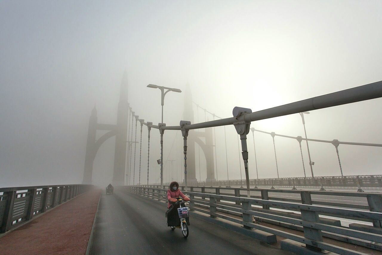 bicycle, bridge - man made structure, transportation, real people, one person, railing, riding, cycling, mode of transport, fog, weather, outdoors, day, rear view, lifestyles, land vehicle, sky, full length, built structure, architecture, city, nature, people