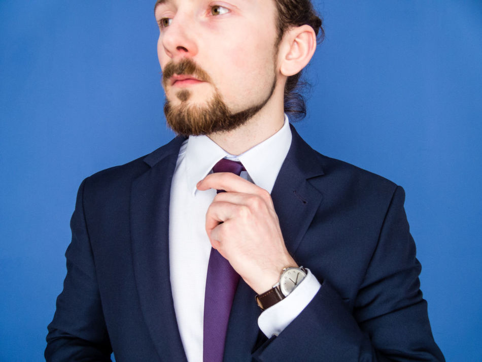 Portrait of a young handsome bearded man in a suit adjusting his tie. Success concept. Beard Blue Boss Business Businessman Confident  EyeEm Best Shots Eyeem Faces Manager Menswear Necktie One Person People Self Portrait Self-Confidence Standing Student Studio Shot Suit Well-dressed White Color Young Adult
