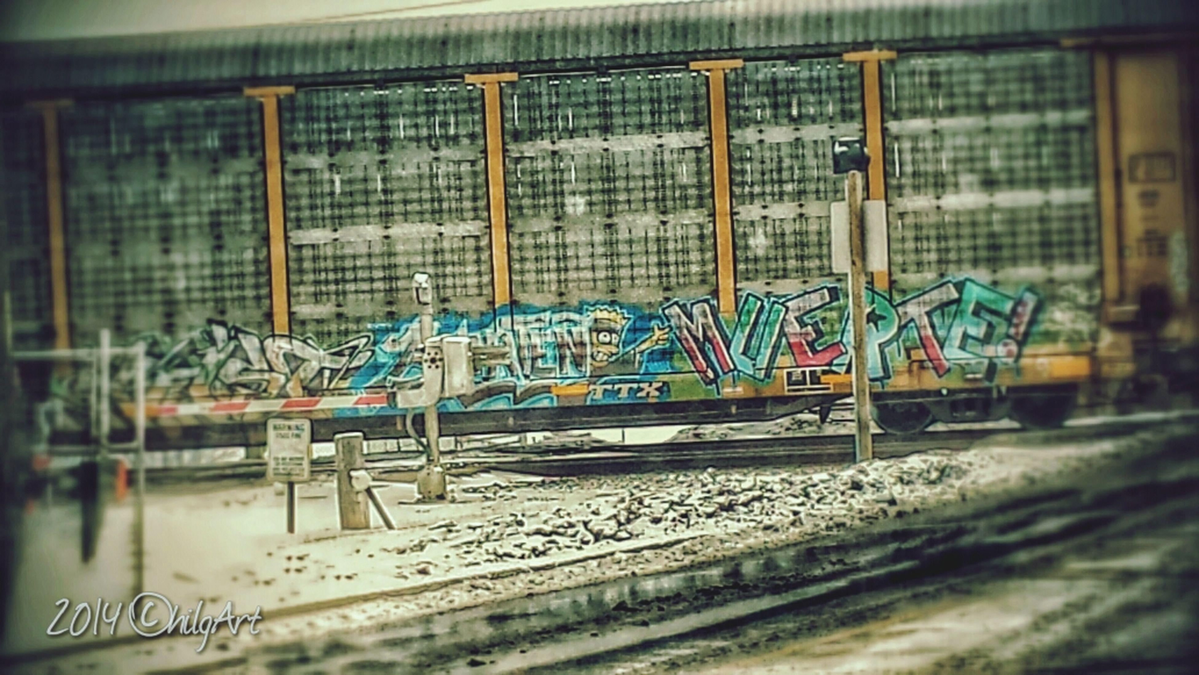 transportation, built structure, indoors, architecture, mode of transport, graffiti, metal, railing, day, empty, no people, absence, public transportation, metallic, land vehicle, window, railroad station platform, railroad station, train - vehicle