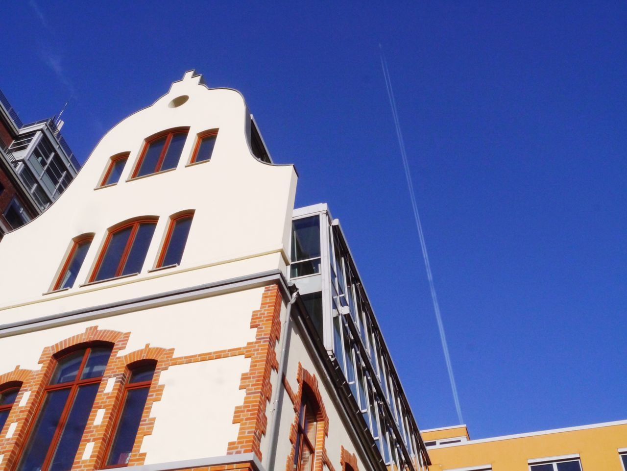 I took this image whilst on an early weekend photo walk. The location is the Medienhafen in Düsseldorf. The colour of the building against the clear blue sky is a lovely contrast. The line in the sky from an aero plane makes for a nice touch. Düsseldorf Color Cityscapes Blue Sky Sunny Day Architecture Buildings Angles Lines Brickwork