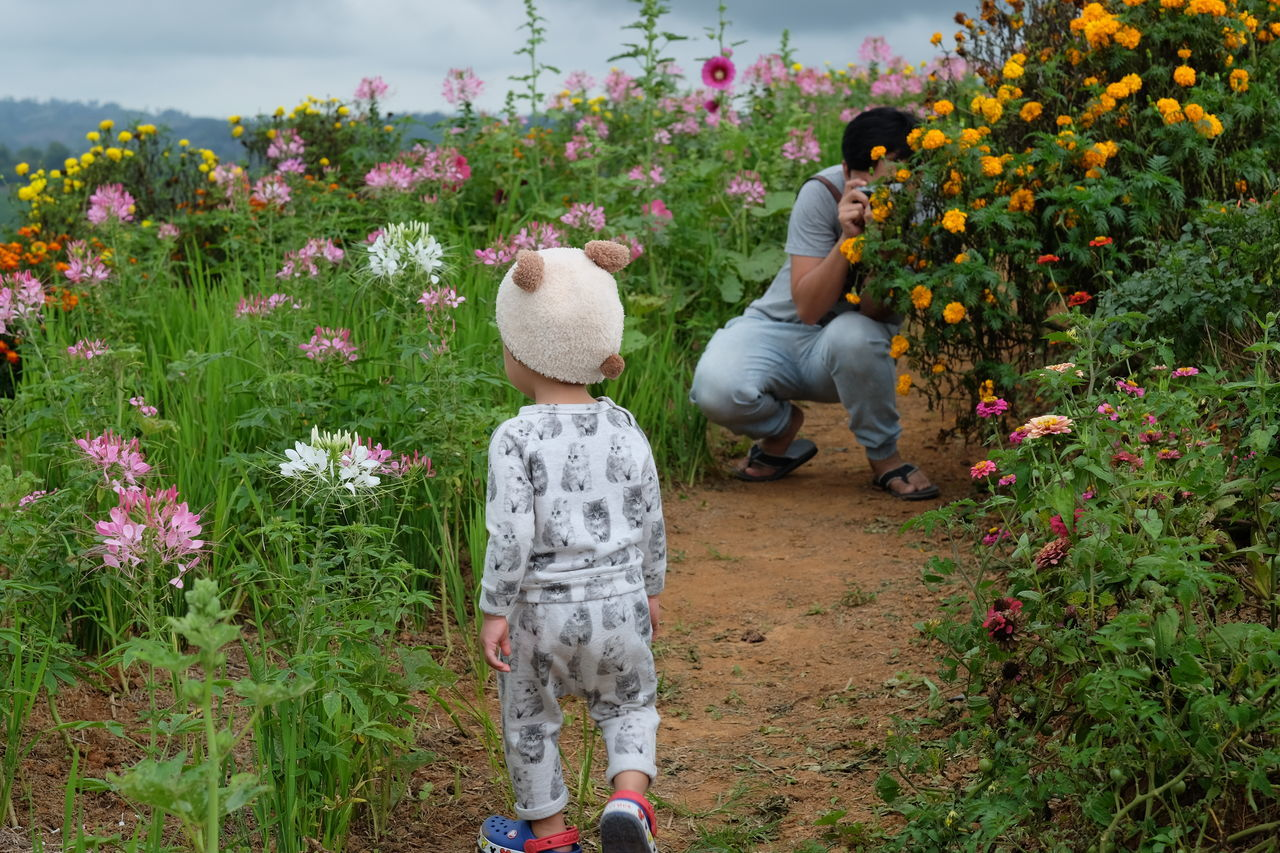 Beauty In Nature Childhood Day Field Flower Fragility Freshness Full Length Grass Growth Men Nature Outdoors People Plant Real People Rear View Togetherness Two People
