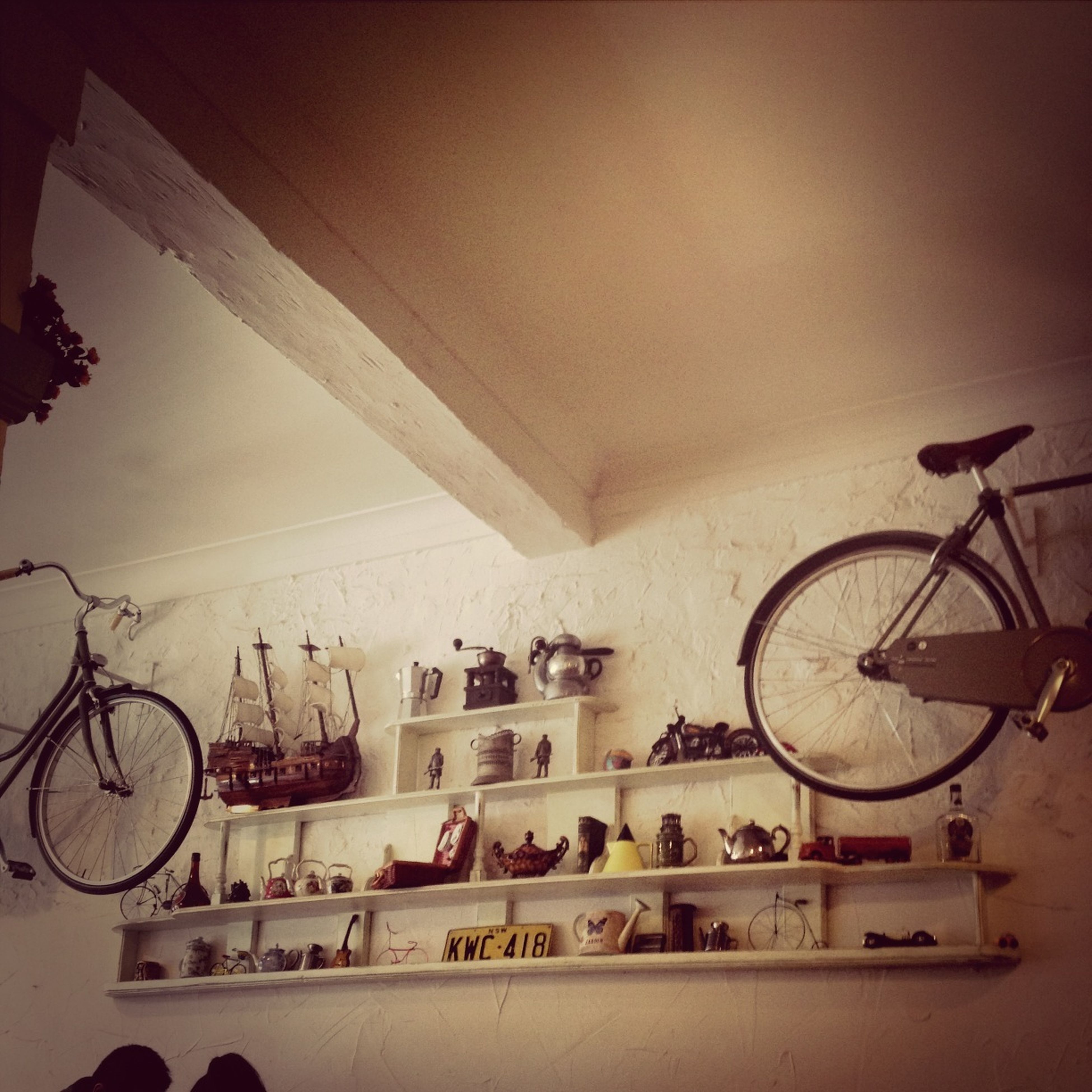 indoors, bicycle, built structure, transportation, architecture, mode of transport, wheel, land vehicle, stationary, wall - building feature, parking, circle, clock, day, no people, wall, low angle view, parked, railing, travel