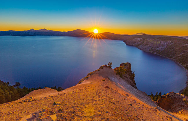 Deep Blue and Orange | The lake was so blue that even when the sky was getting utterly soaked in orange, the deep blue didn't fade much. But, soon night would fall, and when that happens, the deepest lake in the US will slowly fade into the darkness. Crater Lake National Park, Oregon Adventure Beauty In Nature Blue Caldera Lake Cloudcap Overlook Crater Lake Crater Lake National Park Deep Blue Dusk Lake Landscape Photography Lens Flare Mountain Range Nature Non-urban Scene Oregon Rocks Sun Sunset Tourism Tranquil Scene Travel Travel Destinations Volcano Water