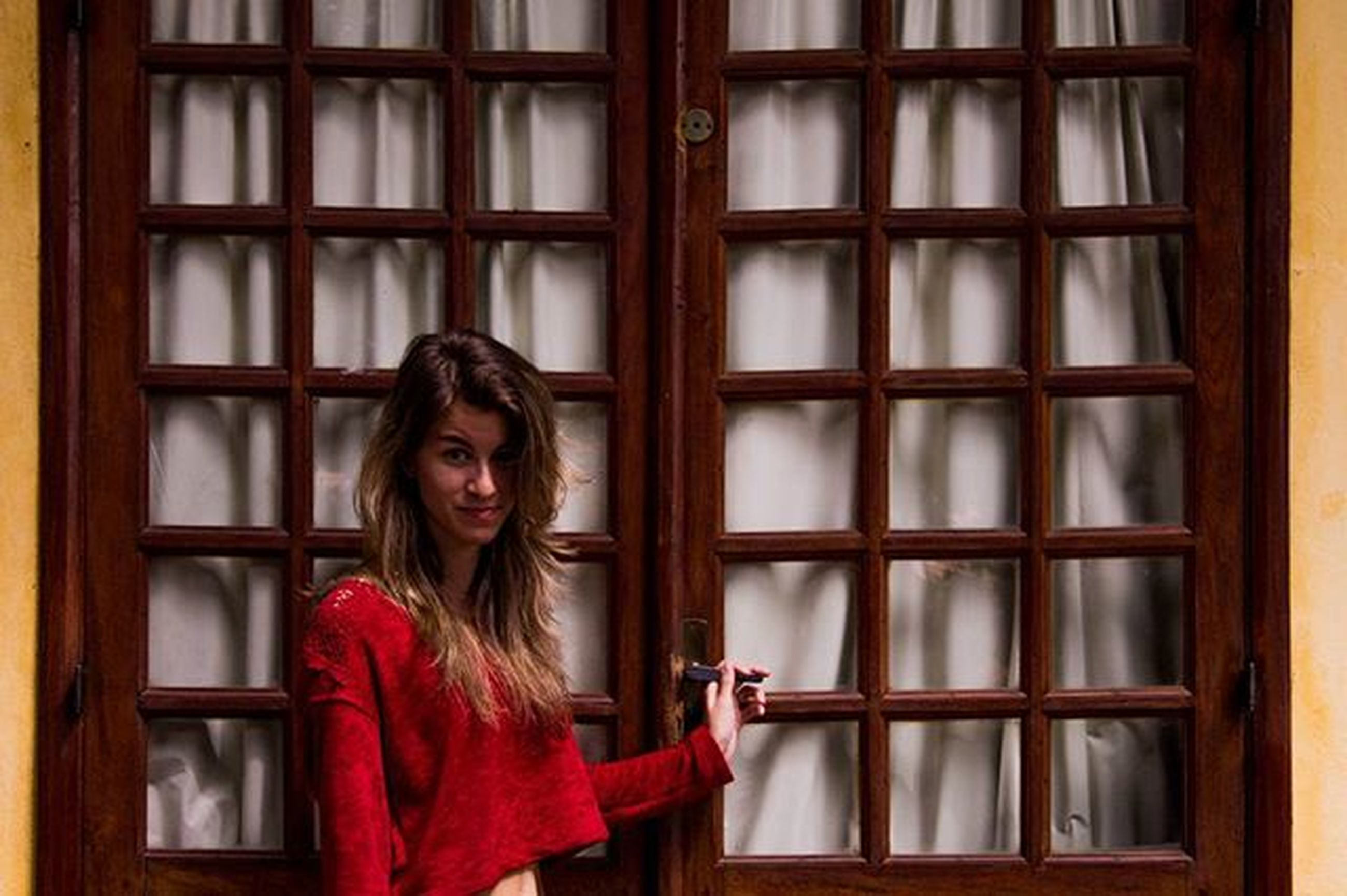 young adult, young women, lifestyles, window, person, looking at camera, front view, portrait, architecture, long hair, leisure activity, building exterior, built structure, indoors, casual clothing, standing, smiling