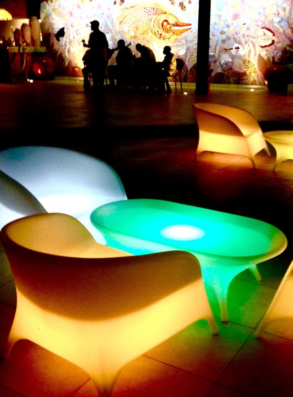 indoors, illuminated, real people, table, night, multi colored, men, close-up, one person, people
