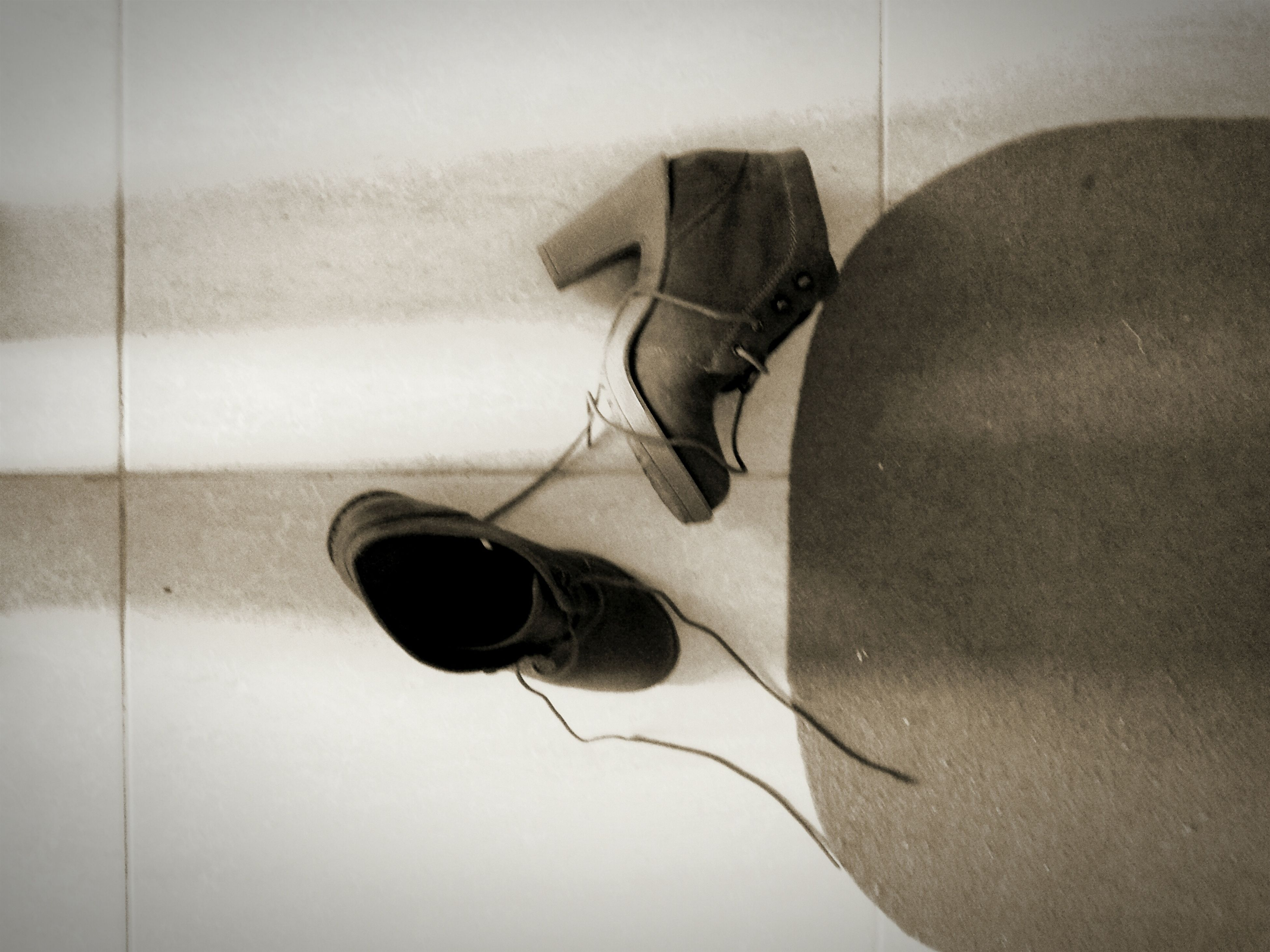 indoors, still life, wall - building feature, shoe, close-up, high angle view, man made object, single object, pair, shadow, hanging, equipment, no people, technology, simplicity, cable, electricity, footwear, wall, flooring