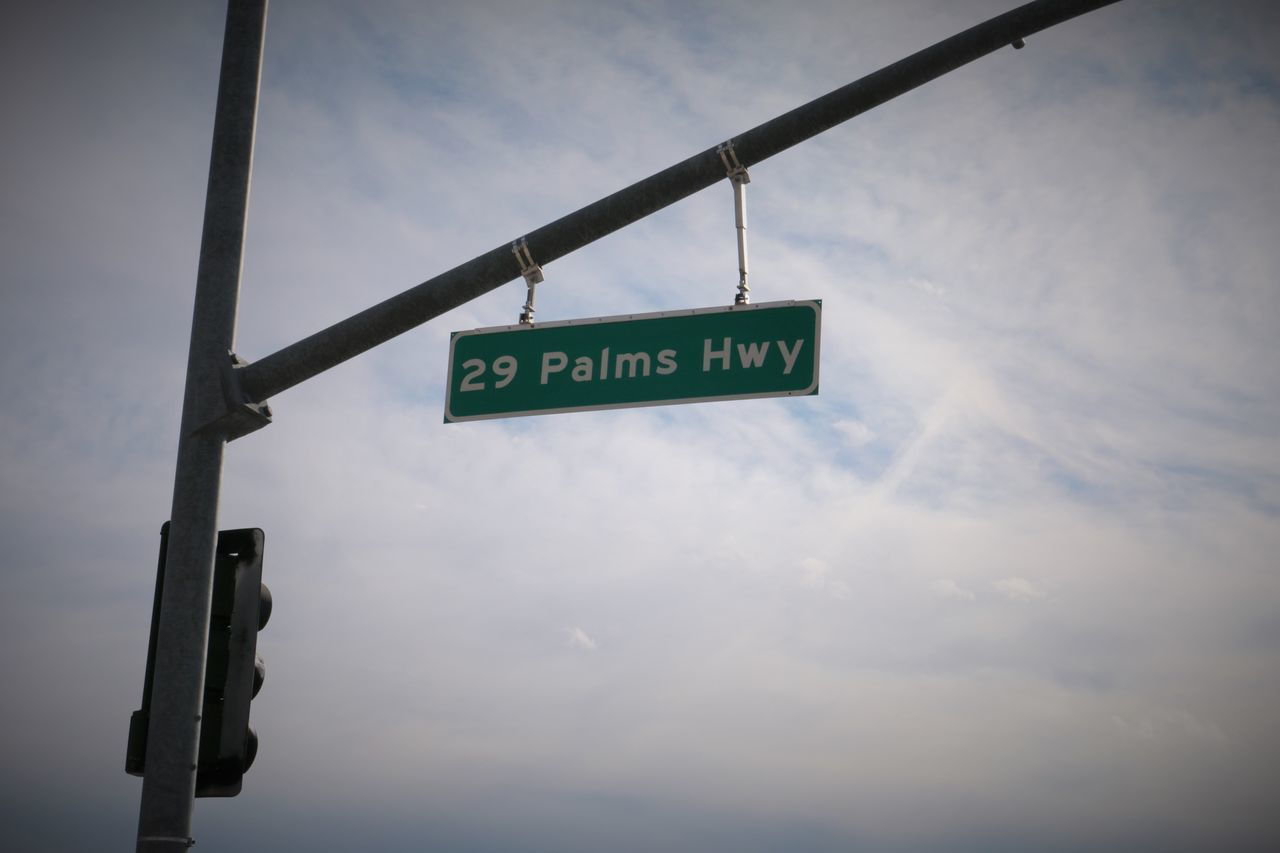 The road sign for 29 Palms Highway 29 Palms Highway Cloud - Sky Day Low Angle View No People Outdoors Sky Street Sign Text Traffic Light