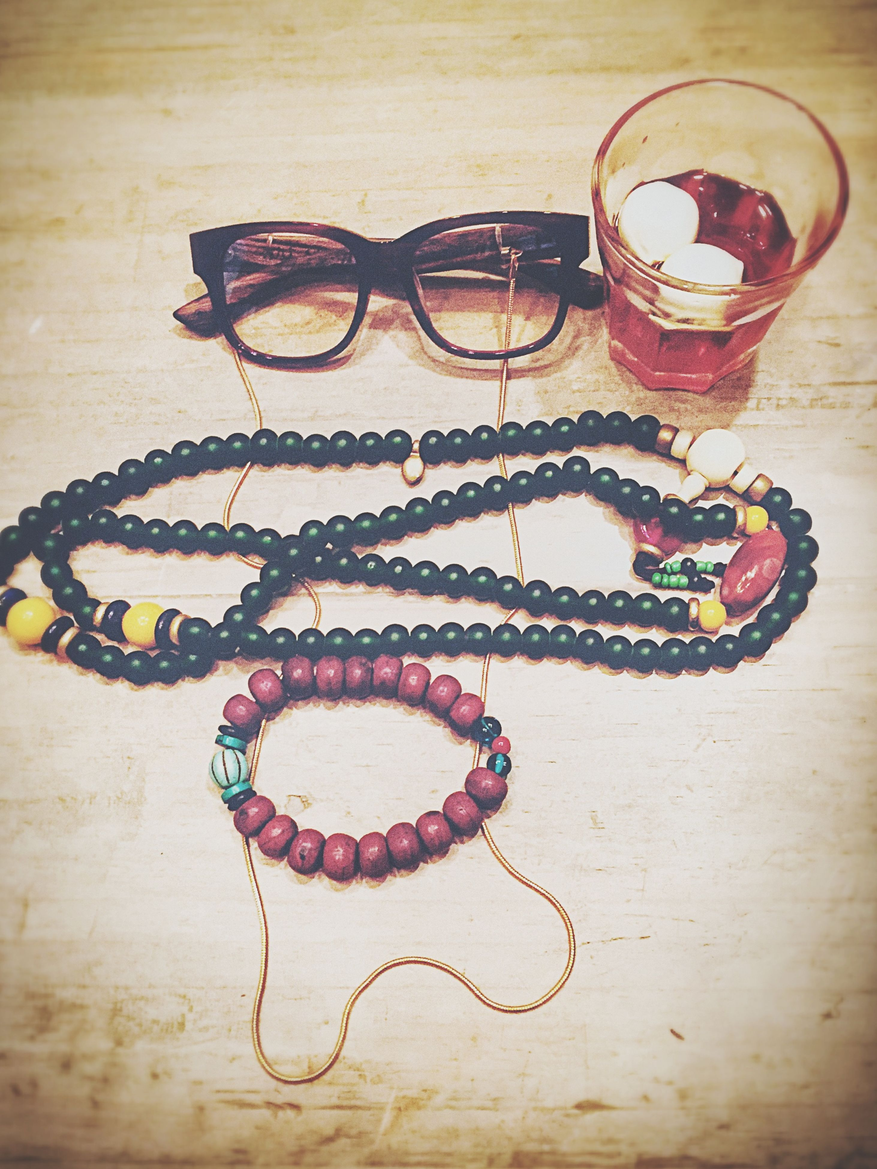 indoors, table, still life, drink, close-up, high angle view, food and drink, heart shape, art and craft, sunglasses, wood - material, creativity, art, decoration, drinking glass, glass - material, no people, refreshment, floral pattern, fashion