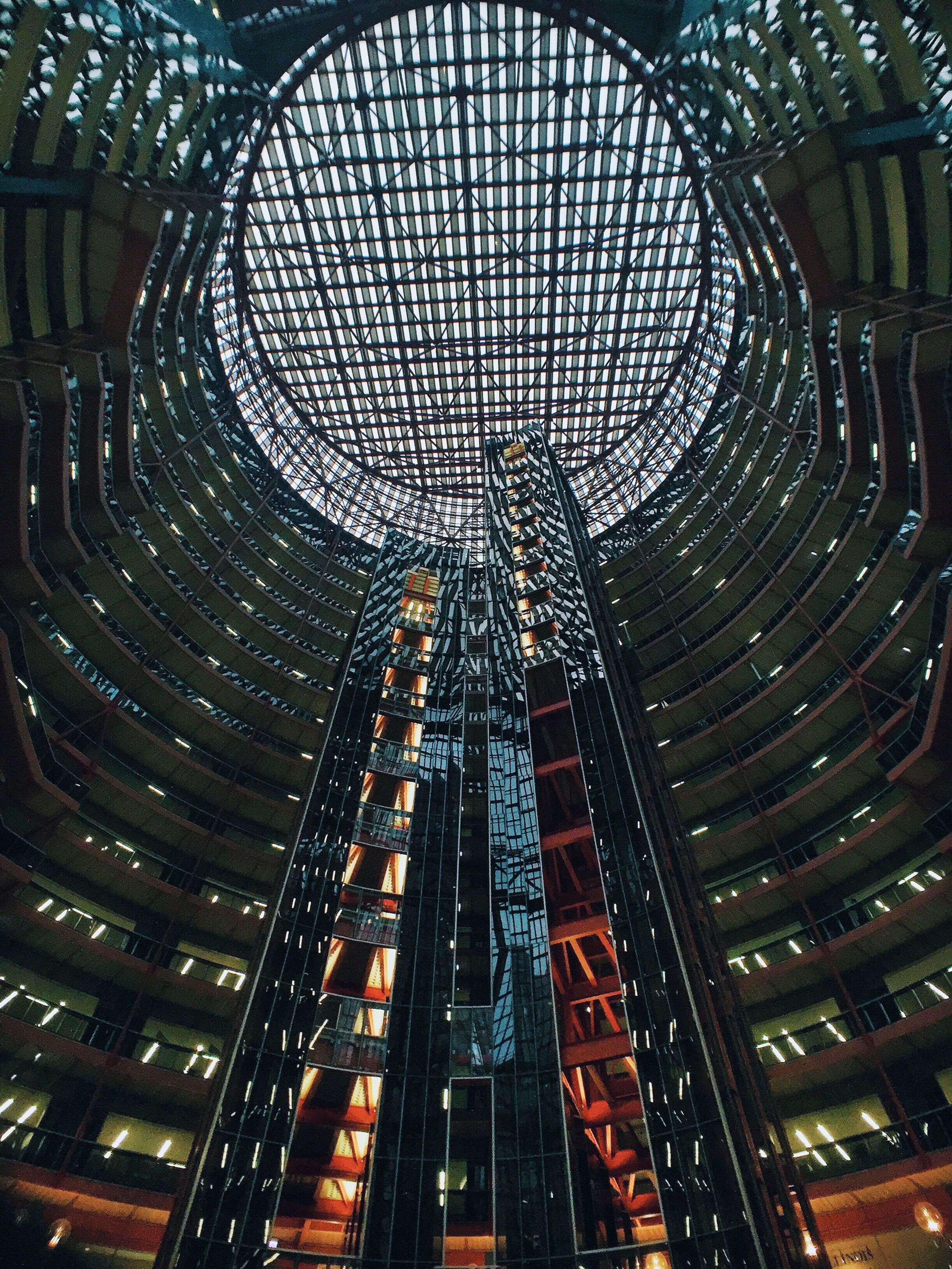 architecture, built structure, low angle view, indoors, modern, pattern, ceiling, architectural feature, building exterior, famous place, skyscraper, illuminated, tall - high, travel destinations, city, tower, glass - material, international landmark, capital cities, design