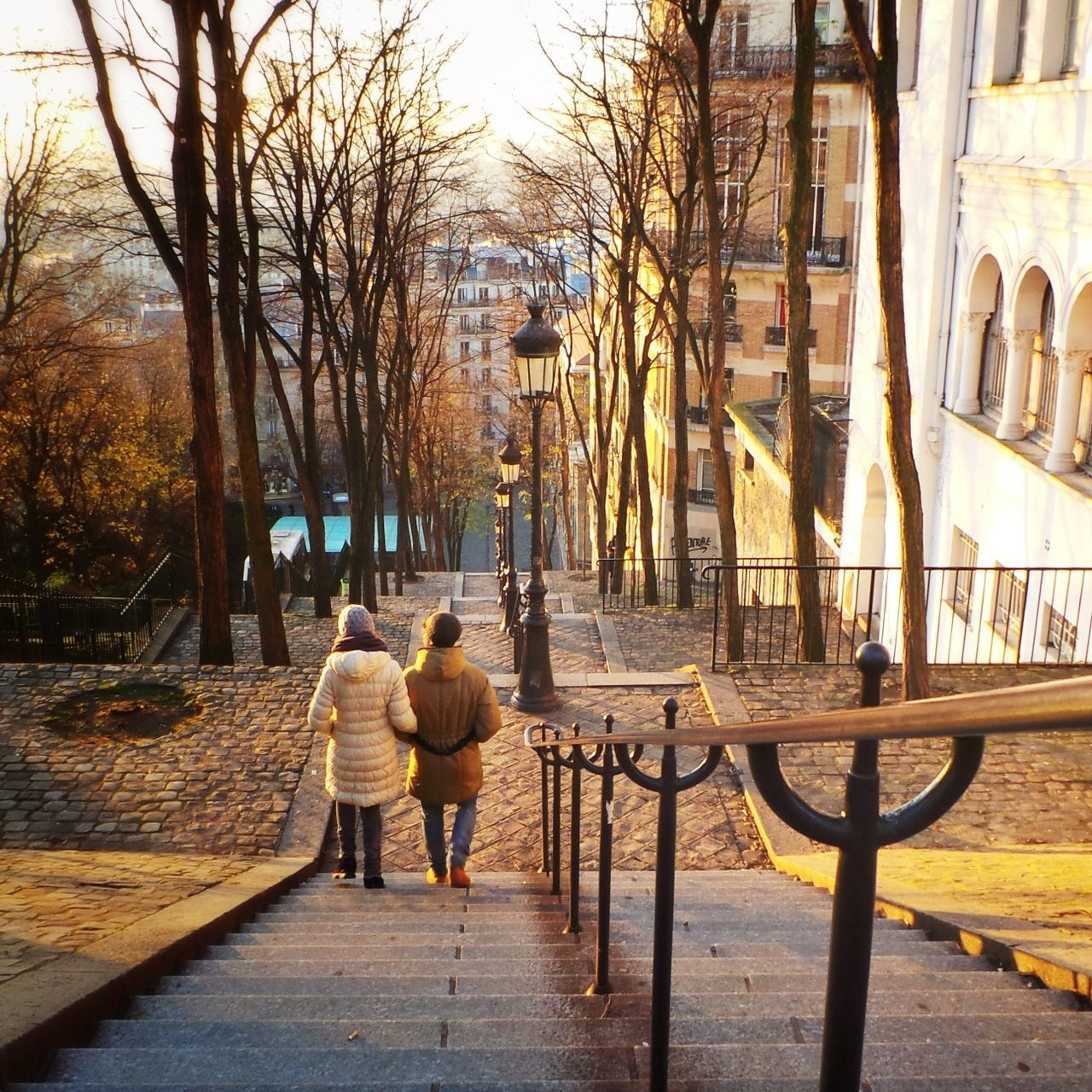 Rear View Of Man And Woman Walking On Steps In City During Morning
