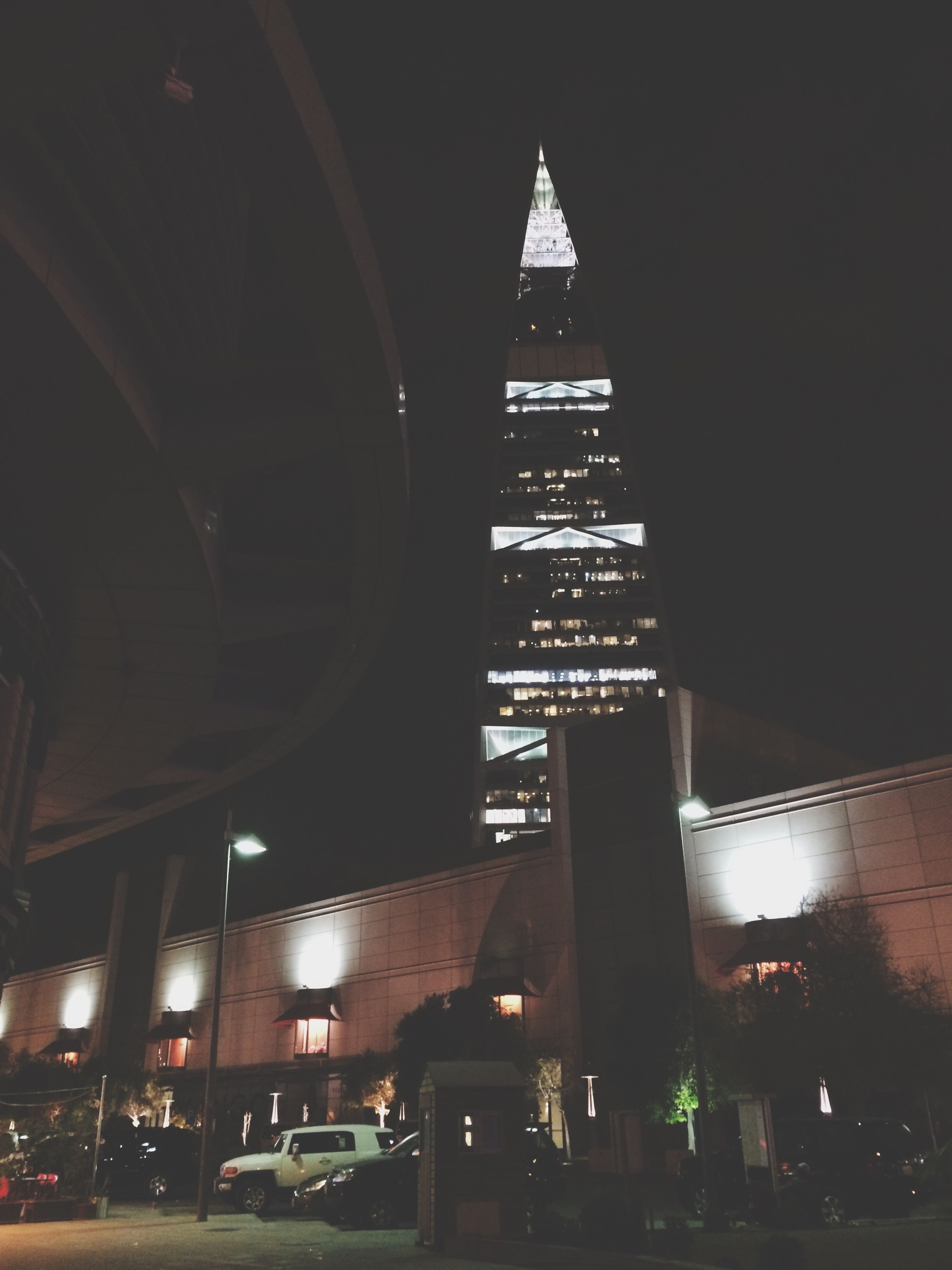 architecture, built structure, building exterior, illuminated, night, city, transportation, street, car, low angle view, land vehicle, mode of transport, dark, skyscraper, tall - high, outdoors, city life, tall, sky, office building, diminishing perspective, the way forward, no people, spire, modern