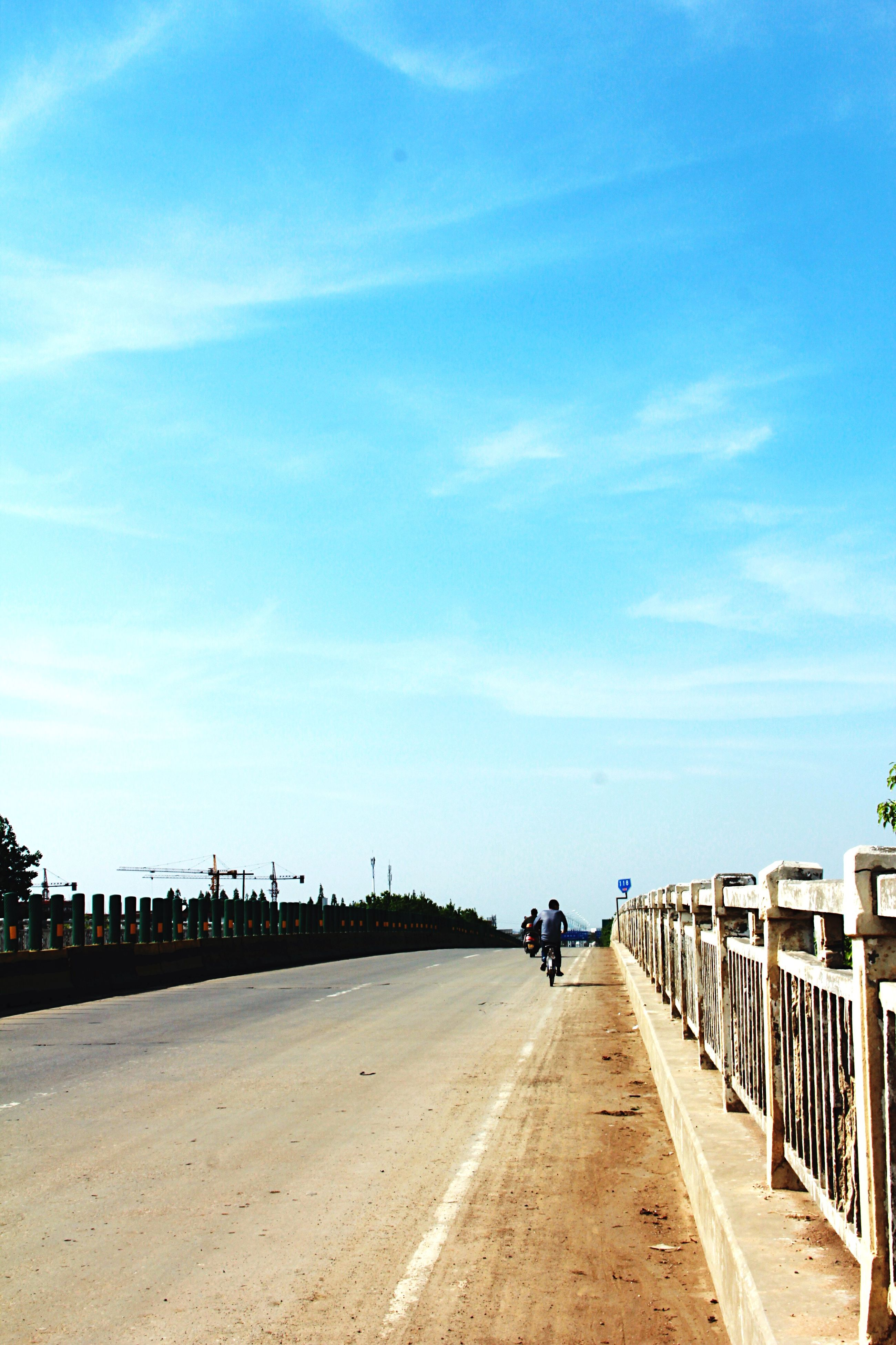 the way forward, sky, diminishing perspective, vanishing point, transportation, road, incidental people, railing, tranquility, nature, long, tranquil scene, empty, blue, walkway, footpath, built structure, cloud - sky, outdoors