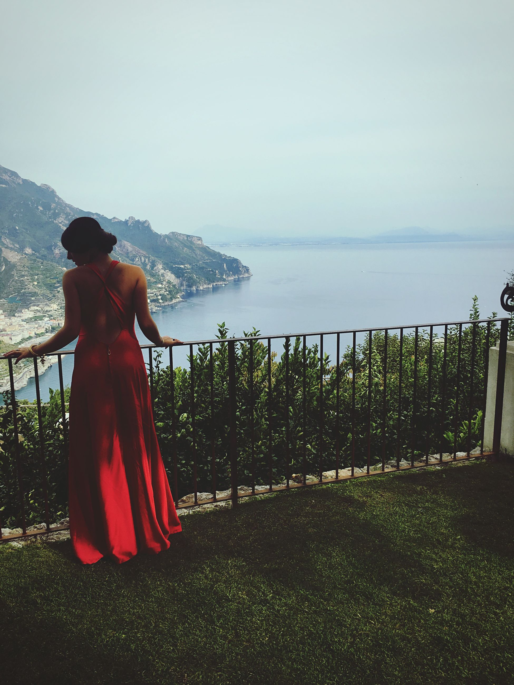 water, rear view, full length, sea, standing, tranquil scene, relaxation, looking at view, scenics, leisure activity, tranquility, lake, vacations, person, beauty in nature, coastline, casual clothing, day, getting away from it all, tourism, summer, nature, cliff, outdoors, carefree, weekend activities, non-urban scene