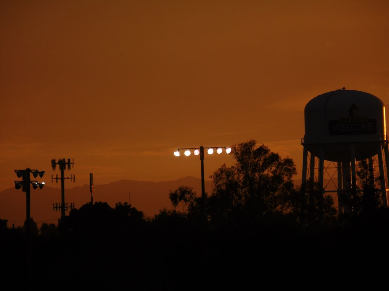 silhouette, sunset, tree, orange color, nature, beauty in nature, communication, no people, tranquility, sky, outdoors, built structure, scenics, architecture, water tower - storage tank, basketball - sport, day