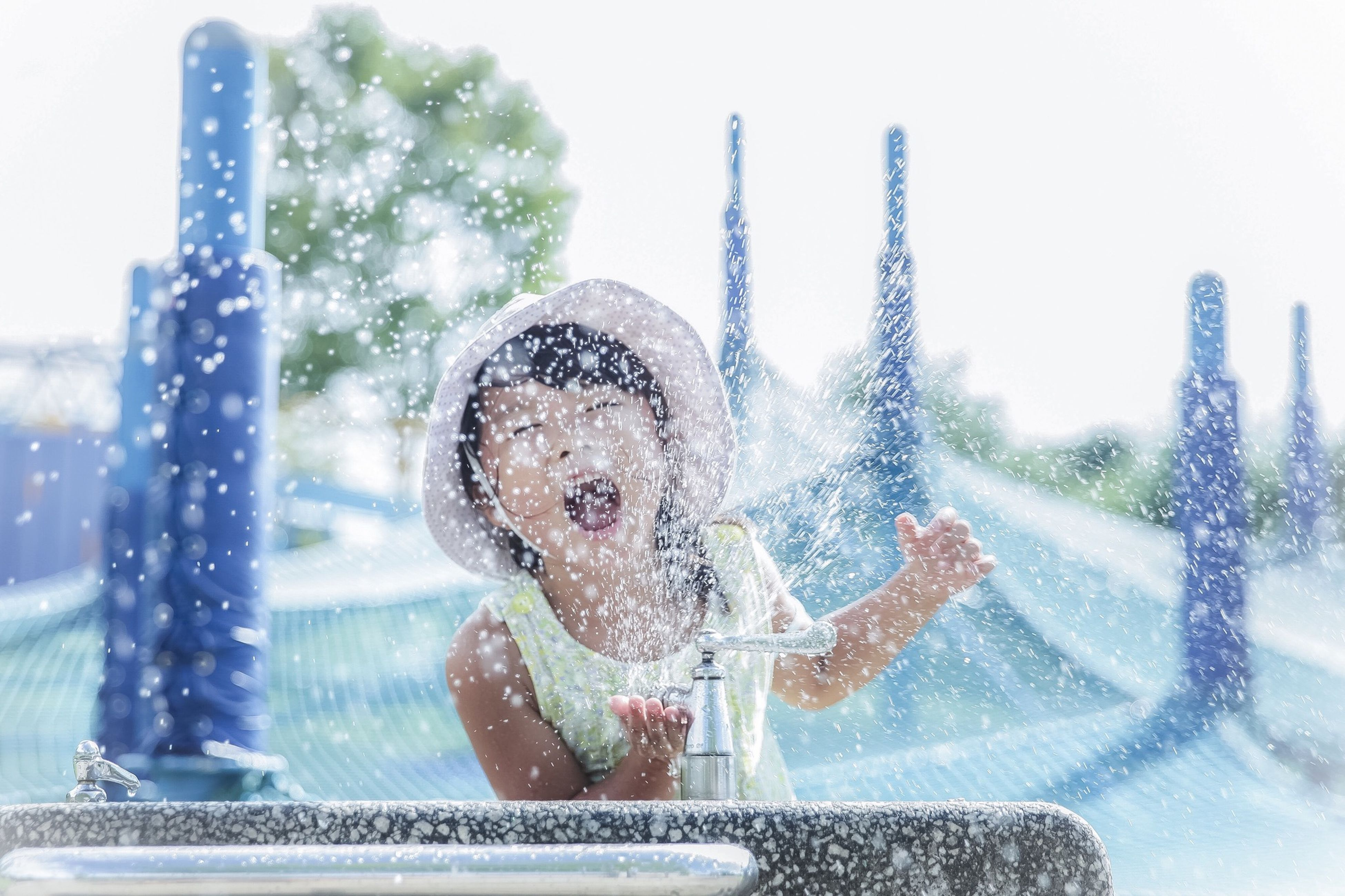 childhood, elementary age, motion, lifestyles, leisure activity, playful, enjoyment, person, girls, wet, playing, water, spraying, fun, focus on foreground, splashing, washing, fountain, day, long hair, joy, enjoying
