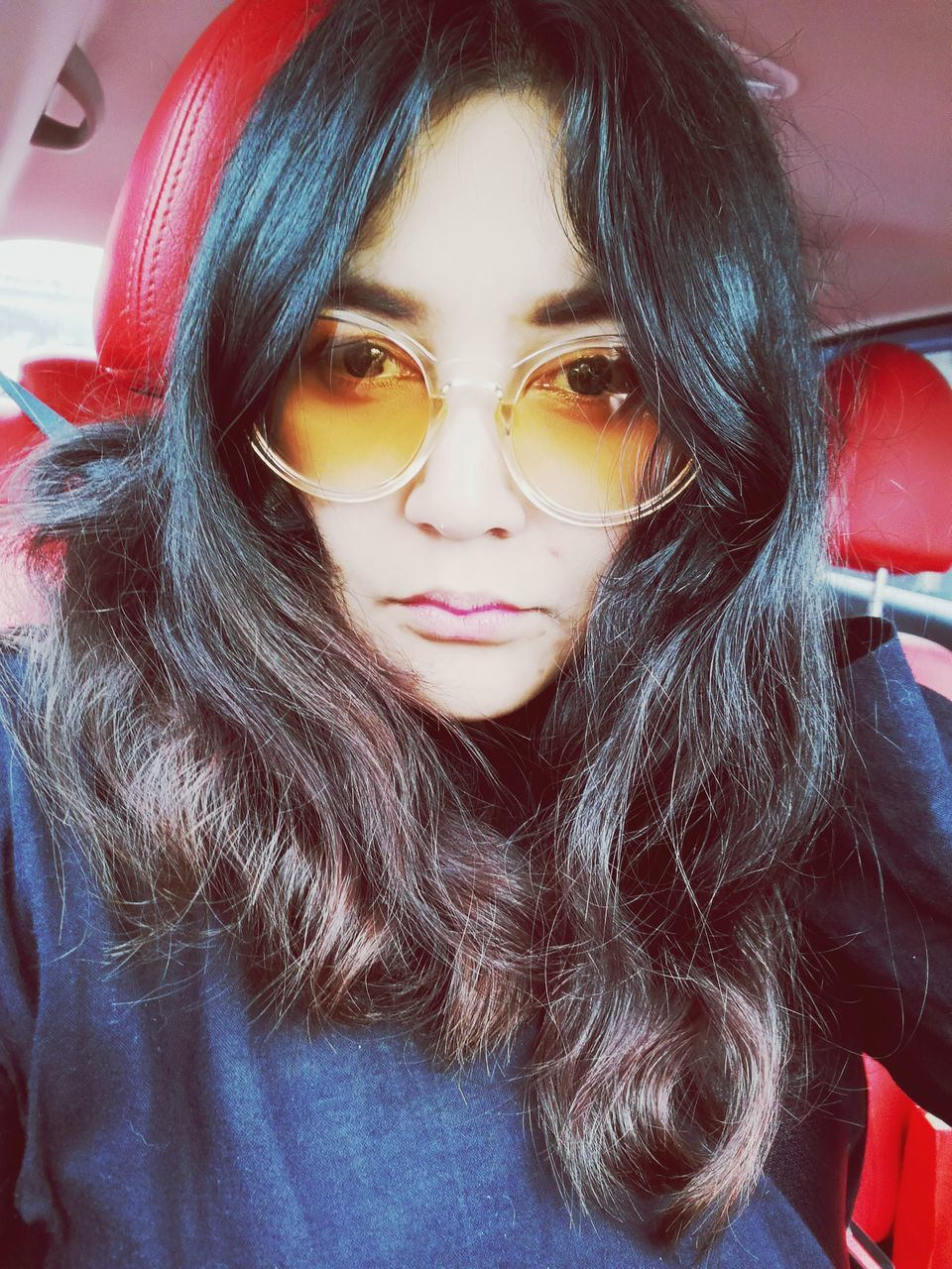 Portrait Of Young Woman Wearing Sunglasses Sitting In Car
