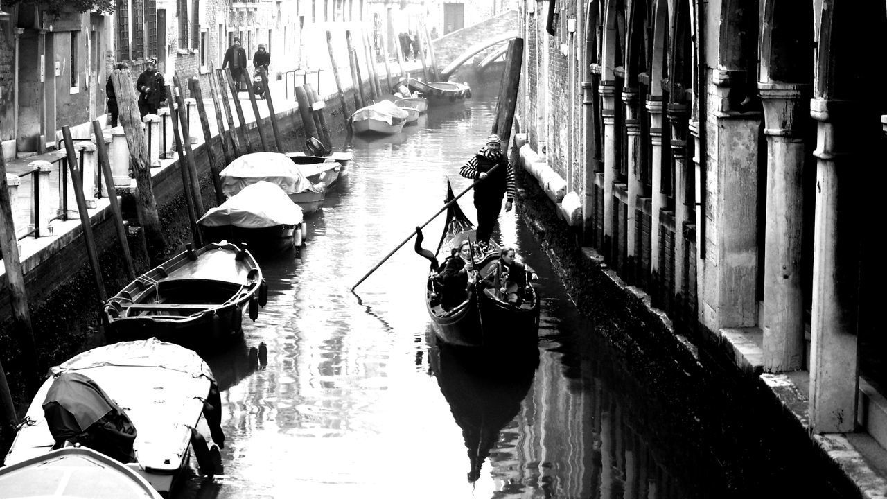transportation, mode of transport, gondola - traditional boat, real people, canal, men, gondolier, day, outdoors, nautical vessel, gondola, architecture, built structure, wooden post, building exterior, water, adult, people