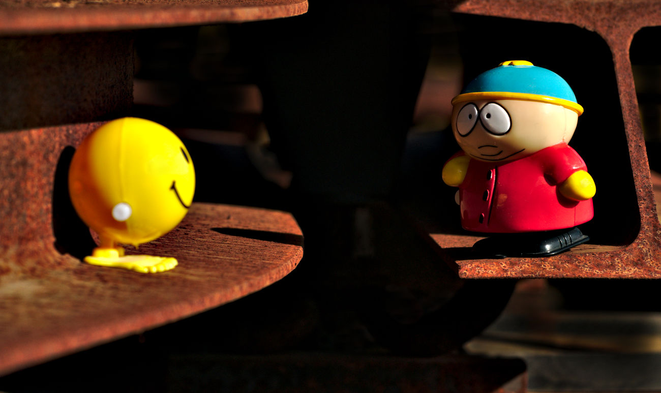 On The Railroad Best Friends Challenge Close Up Eric Eric Cartman Extreme Light Figurine  Focus On Foreground From My Point Of View Iron Bars Light And Shadow Nikon Red Rusty Rusty Iron Scenary Selective Focus Smiley Face Still Life Talking Photos Toy Toy Adventures Toy Story Untold Stories Yellow
