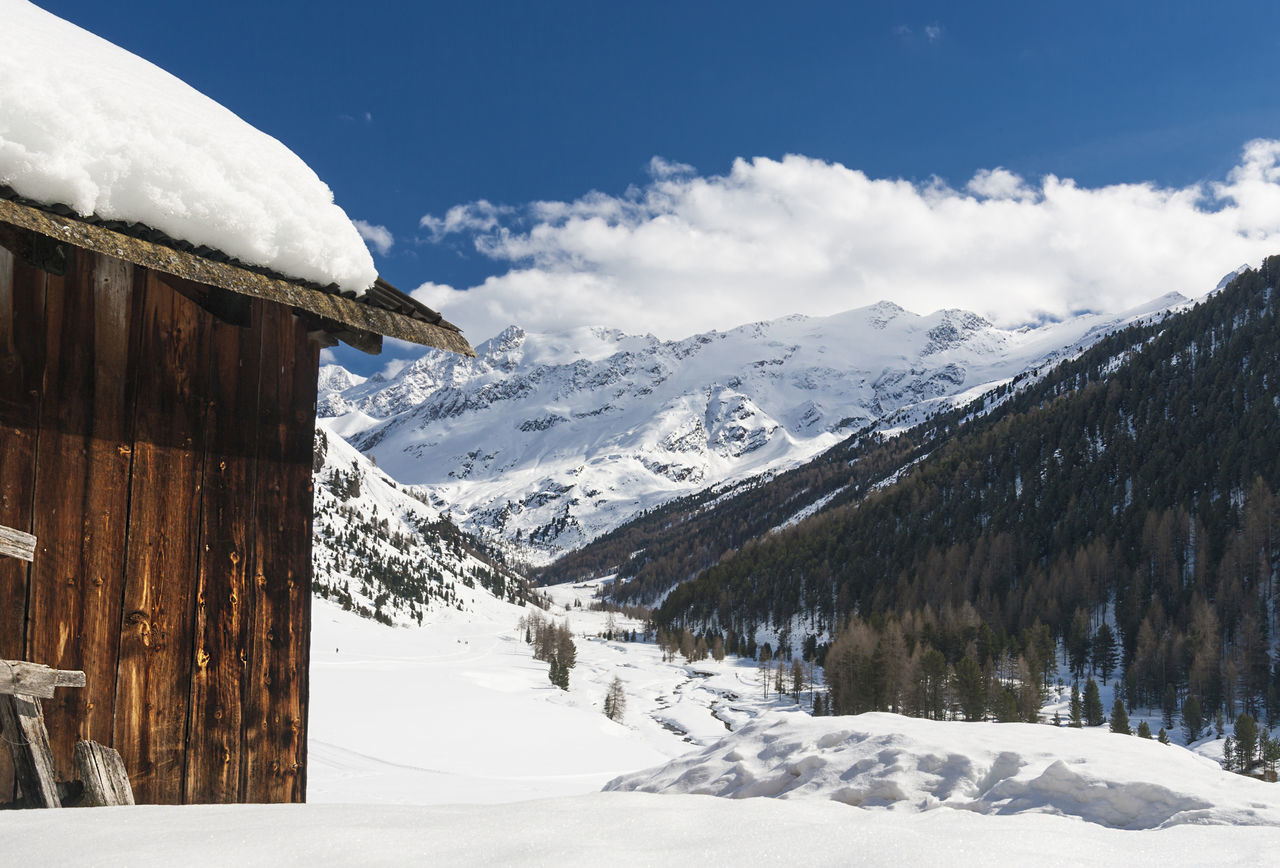 Log Cabin On Snowcapped Mountain Against Sky