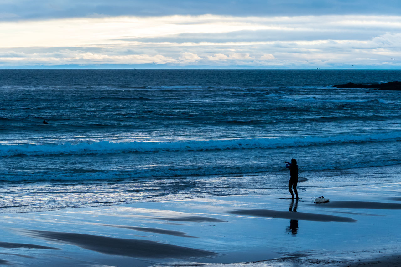 sea, water, beach, horizon over water, nature, sky, scenics, real people, one person, beauty in nature, leisure activity, tranquil scene, outdoors, tranquility, cloud - sky, full length, standing, silhouette, lifestyles, day, sport, wave, paddleboarding, people