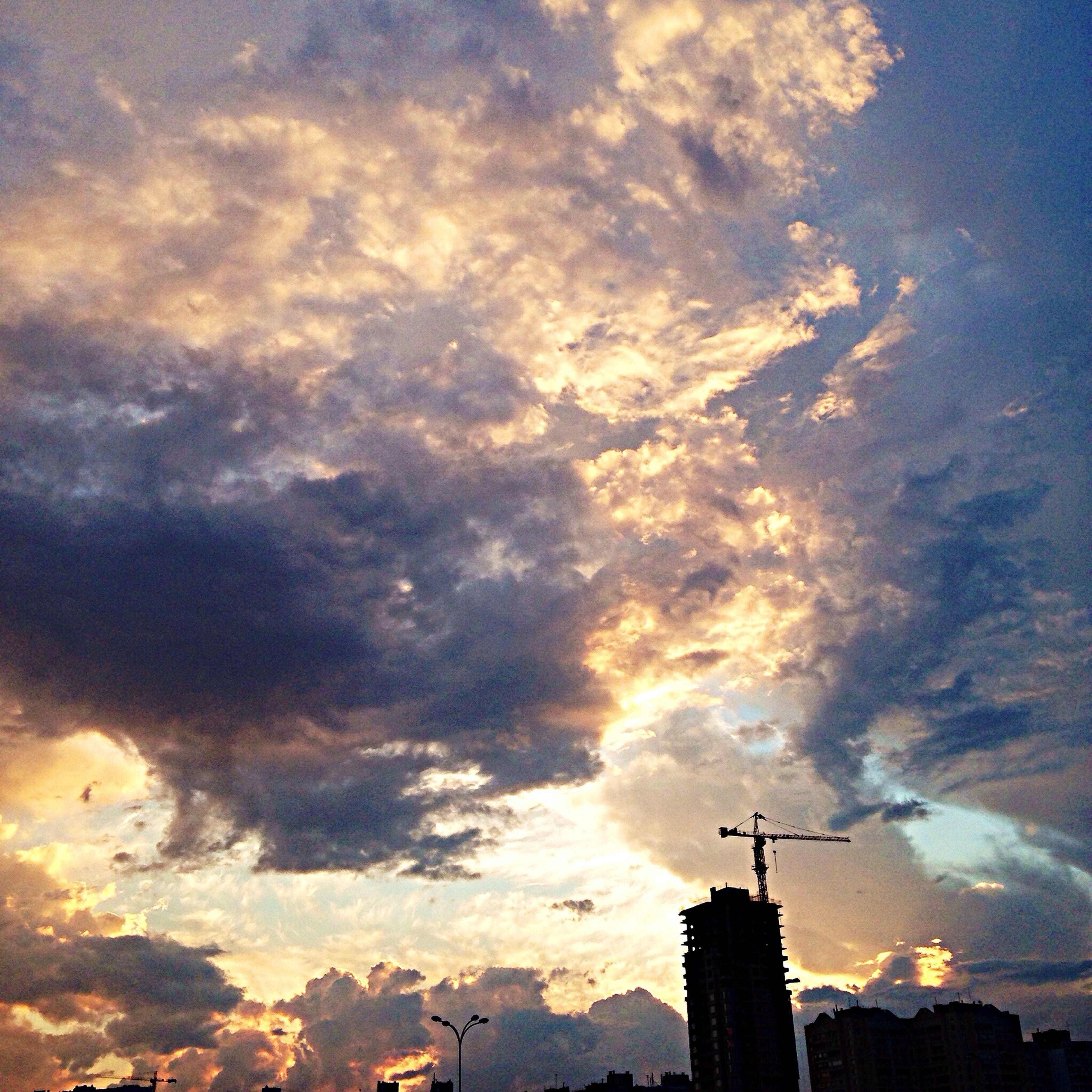 sky, sunset, building exterior, cloud - sky, architecture, built structure, silhouette, cloudy, low angle view, weather, city, cloud, development, dramatic sky, crane - construction machinery, nature, outdoors, no people, orange color, dusk