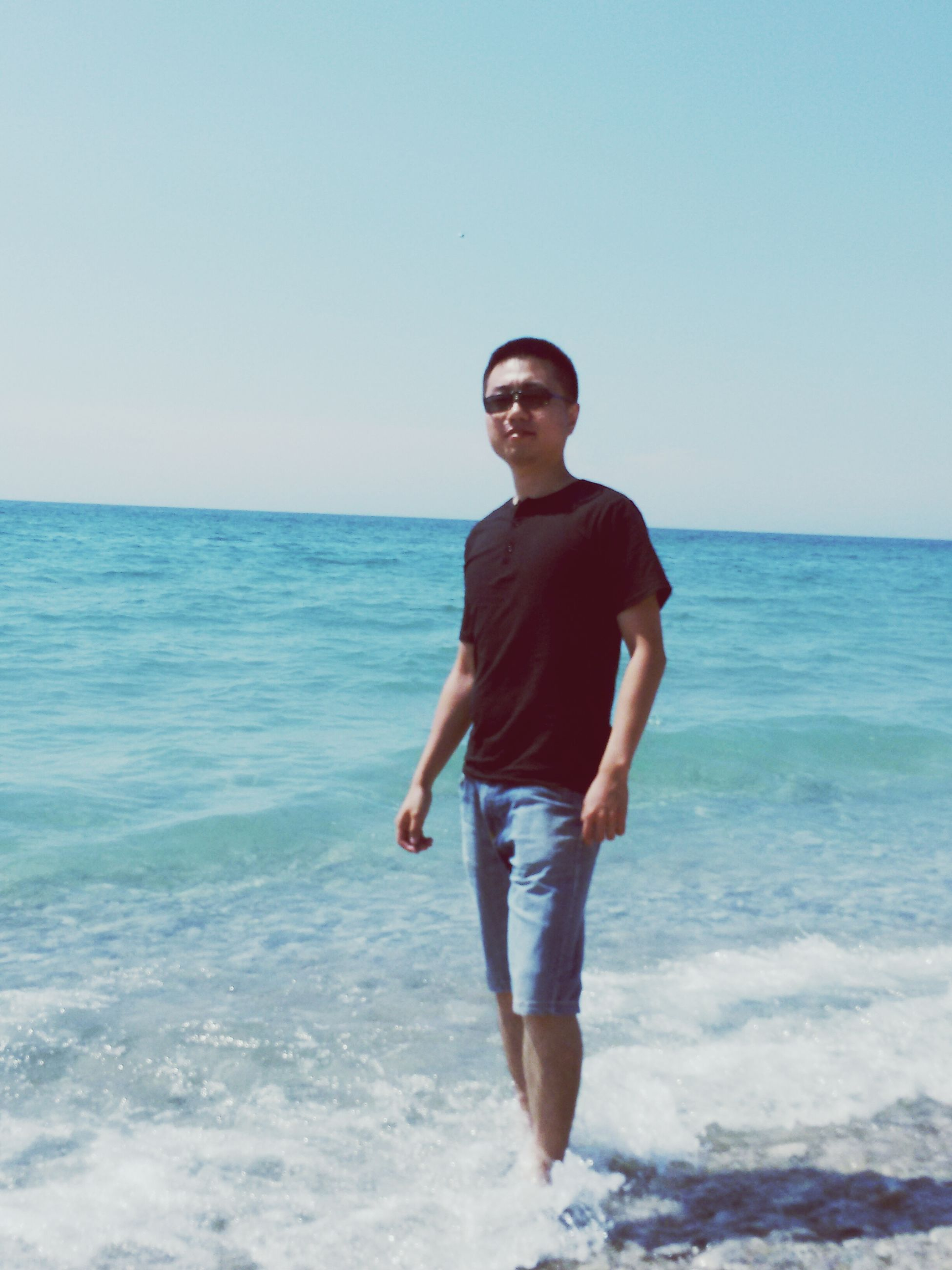 sea, water, portrait, looking at camera, horizon over water, copy space, young adult, person, clear sky, front view, lifestyles, beach, casual clothing, leisure activity, standing, young men, shore, smiling