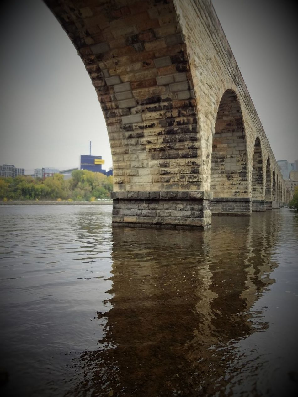 St. Anthony Main trails in Minneapolis MN Arch Architecture Bridge Bridge - Man Made Structure Building Exterior Built Structure Connection Day History Medieval Nature No People Outdoors Reflection Sky Stone Tabphotography Travel Destinations Water Water Reflections Waterfront