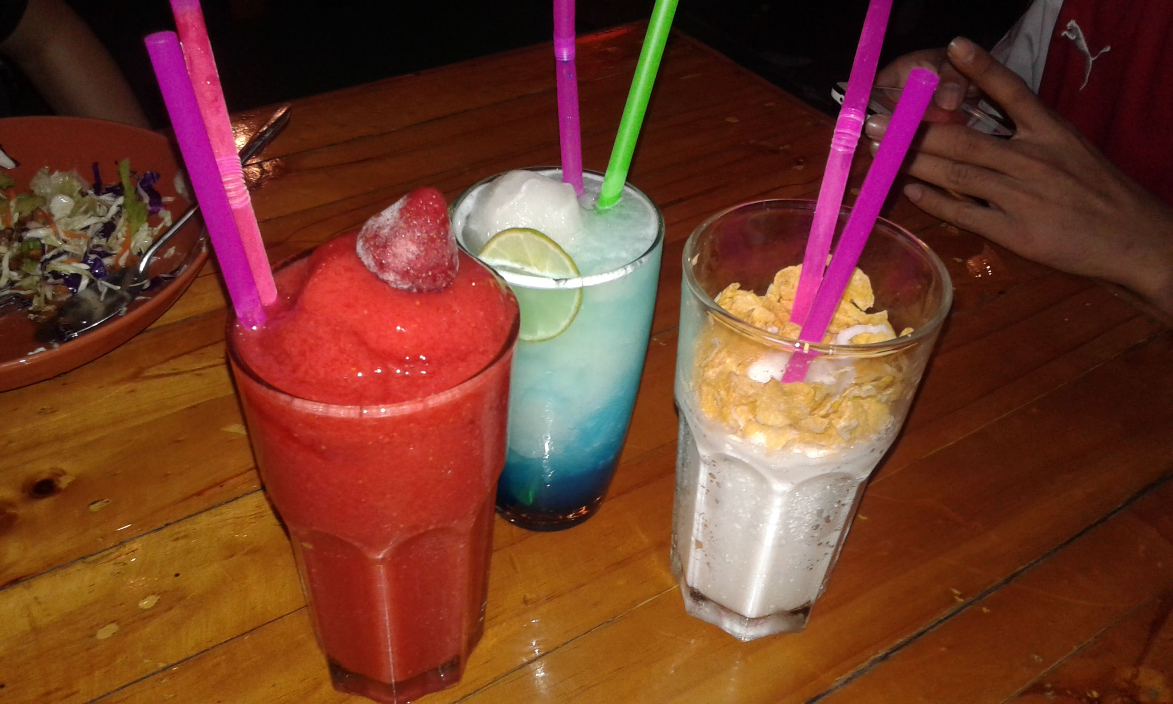 food and drink, table, drink, freshness, drinking glass, indoors, refreshment, drinking straw, still life, wood - material, cocktail, close-up, high angle view, wooden, juice, restaurant, pink color, alcohol, healthy eating, glass - material