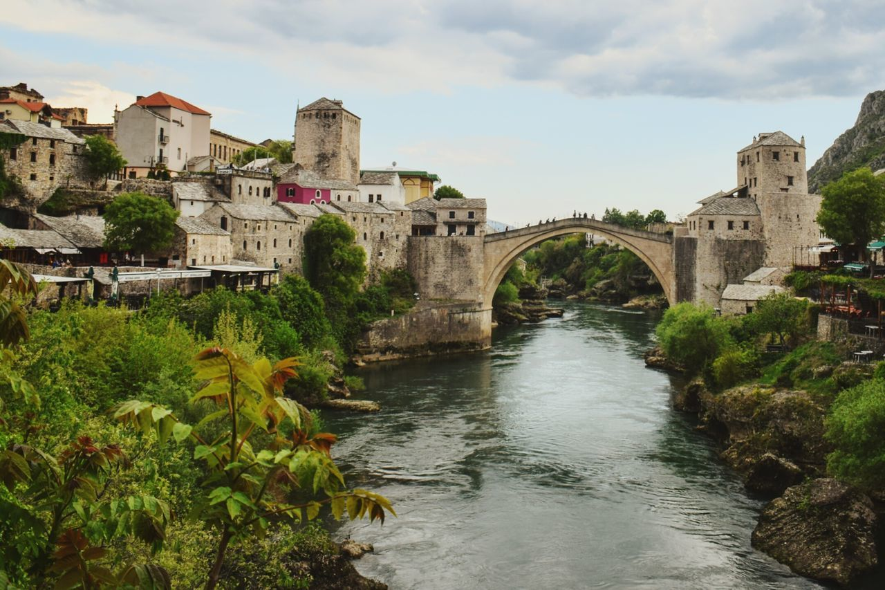 architecture, built structure, bridge - man made structure, connection, sky, water, river, arch, cloud - sky, day, history, outdoors, building exterior, travel destinations, no people, nature, tree