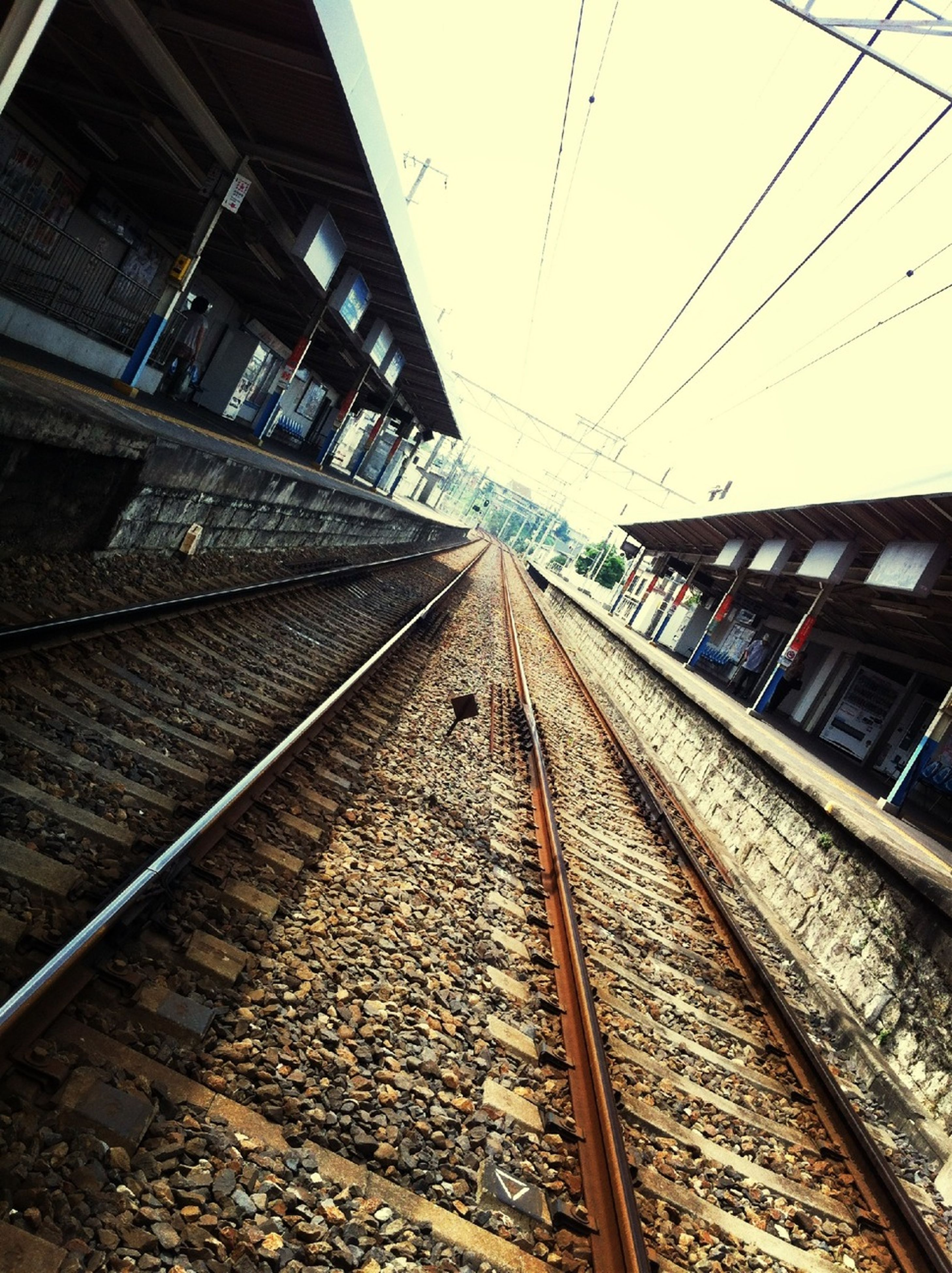 railroad track, rail transportation, transportation, public transportation, railroad station, railroad station platform, the way forward, railway track, diminishing perspective, vanishing point, built structure, power line, architecture, travel, day, cable, no people, connection, sky, electricity