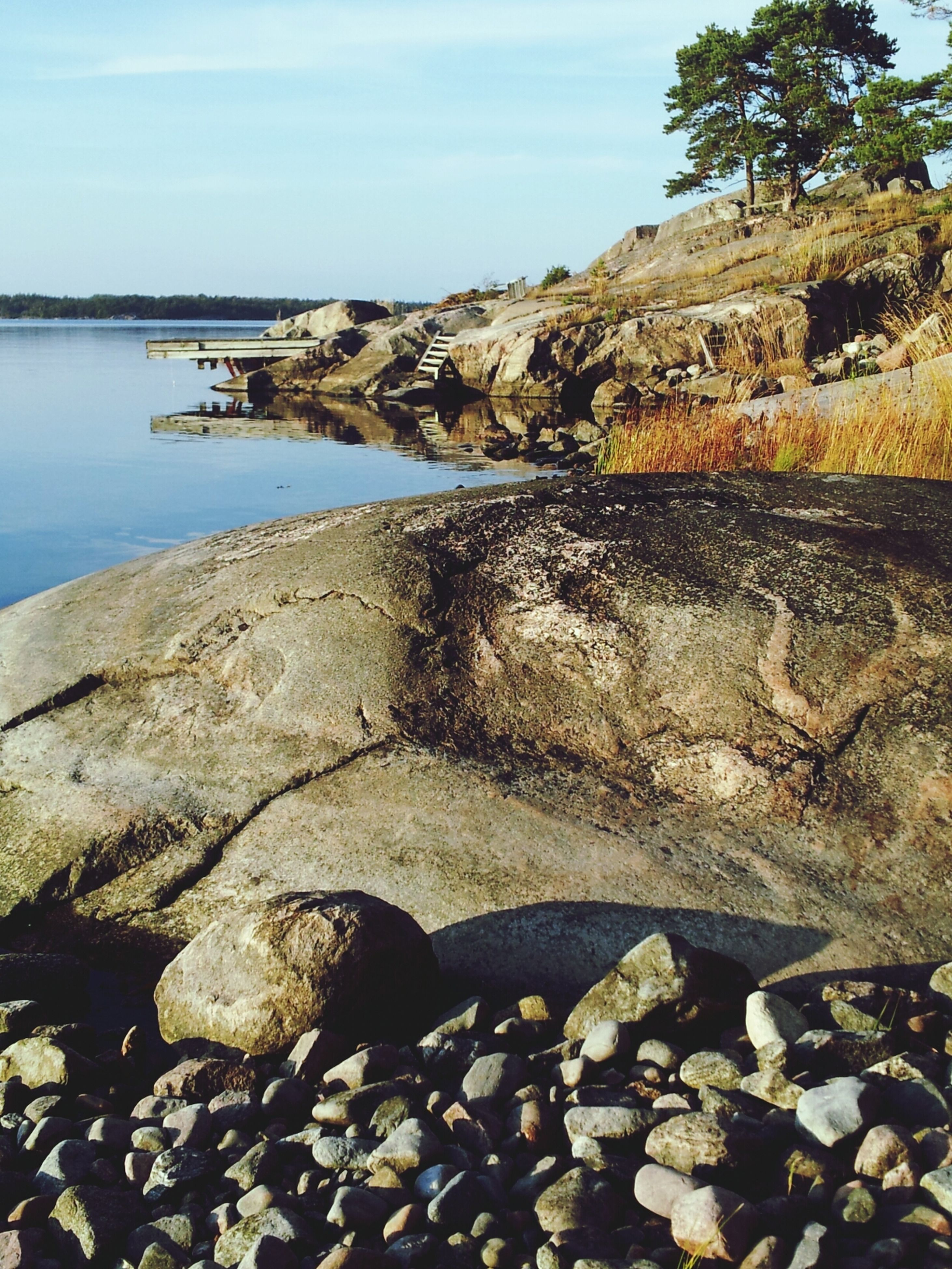 water, rock - object, stone - object, tranquility, sea, tranquil scene, scenics, nature, pebble, stone, sky, beauty in nature, shore, reflection, beach, rock, lake, sunlight, clear sky, river