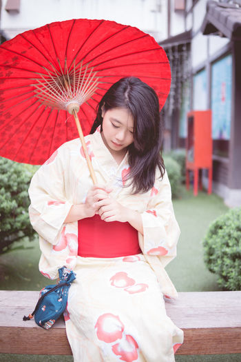 Day Holding Kimono Lifestyles One Person Outdoors People Real People Red Sitting Smiling Three Quarter Length Young Adult Young Women