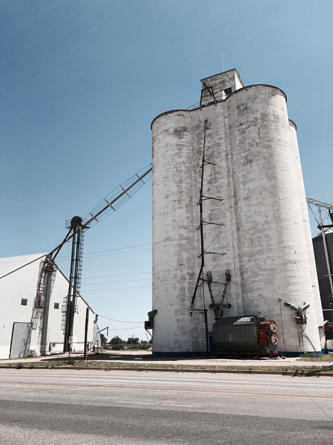 """""""Lone Silo"""" A massive silo, still in use, dominates a tiny village along Route 60 in New Mexico. Industry Architecture Silo Storage Tank Industrial Building  New Mexico Newmexicophotography Route 60 Silos Farming Travel Photography Historical Place"""