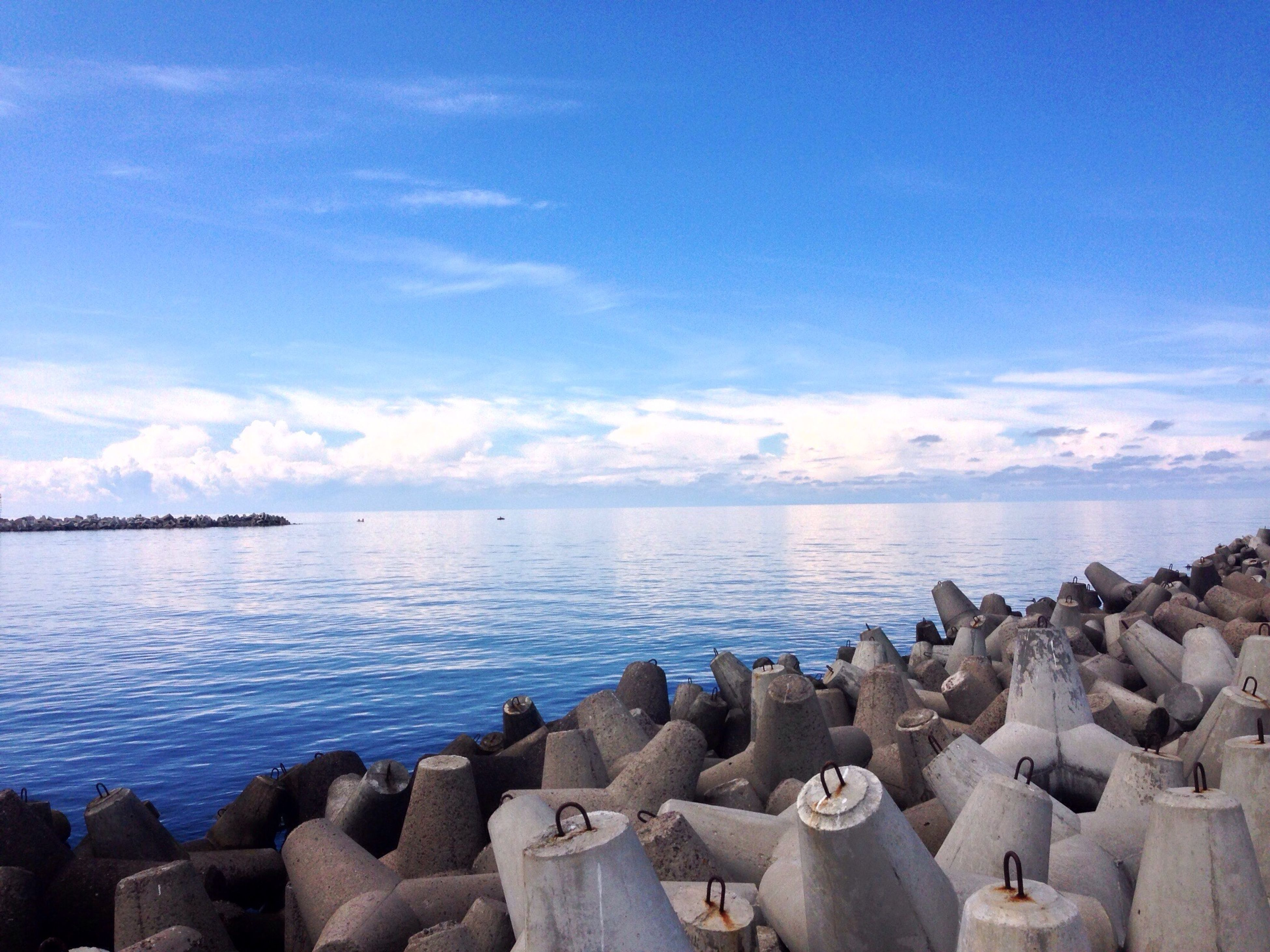 sea, water, horizon over water, sky, scenics, tranquil scene, blue, tranquility, beauty in nature, nature, cloud - sky, rock - object, beach, idyllic, cloud, day, shore, outdoors, sunlight, stone - object