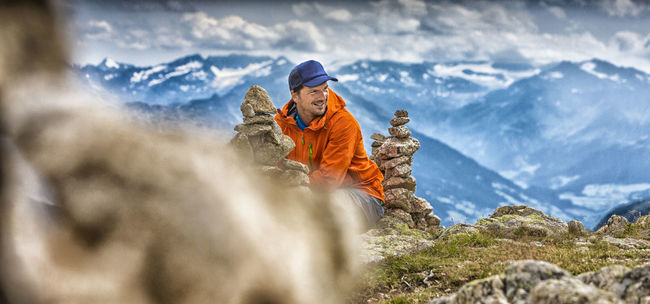 Portait of man sitting on the peak in the Alps Activity Adventure Brixen  Happy Hiker Hiking Man Meran Mountain Range Outdoors Peak Portait Pustertal Relax Selective Focus Sitting Smiling South Tyrol Steinmanderl Steinmännchen Summit Summit View Südtirol Tourism Val Pusteria