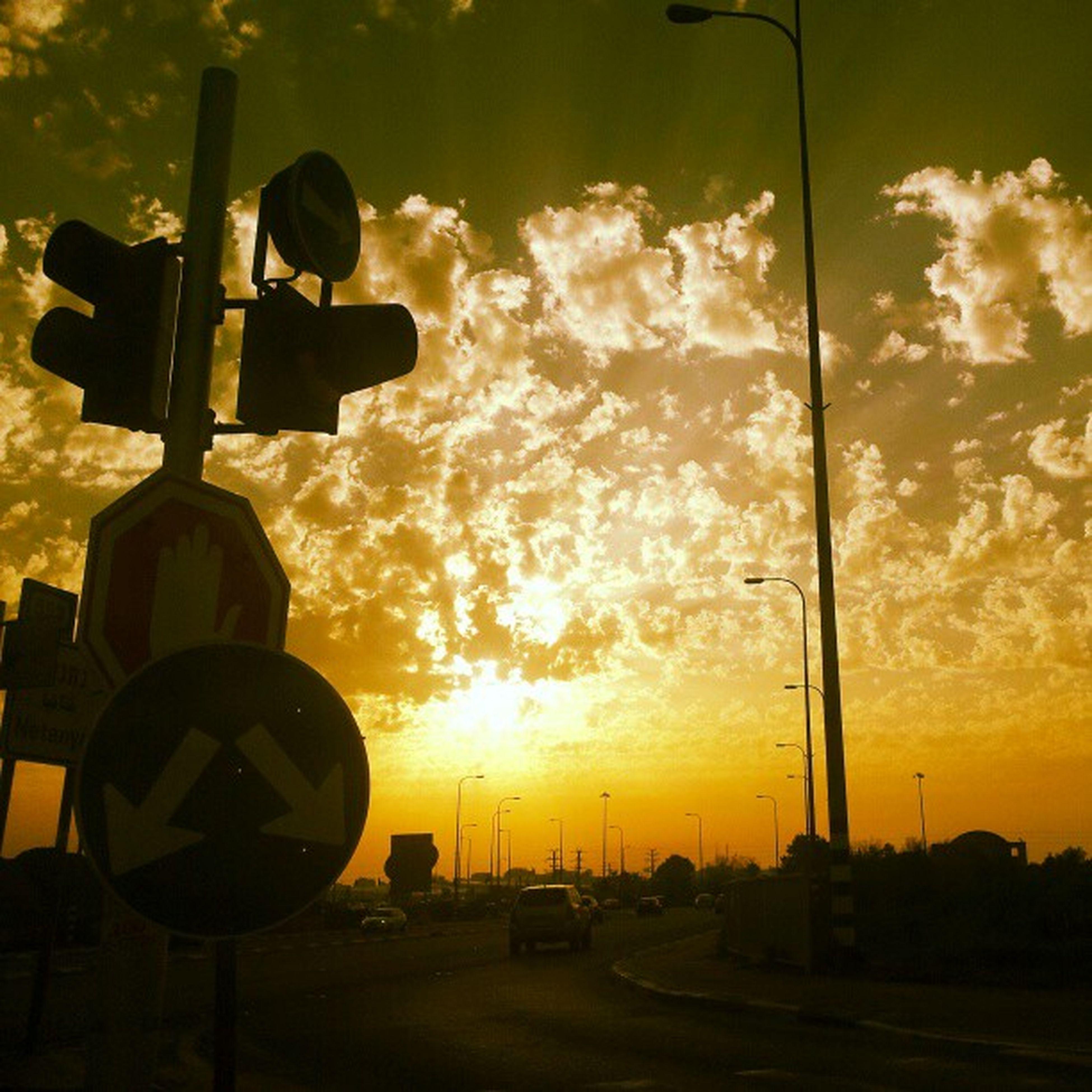 sunset, street light, sky, orange color, silhouette, lighting equipment, cloud - sky, car, sun, land vehicle, transportation, yellow, street, outdoors, nature, illuminated, no people, sunlight, mode of transport, beauty in nature