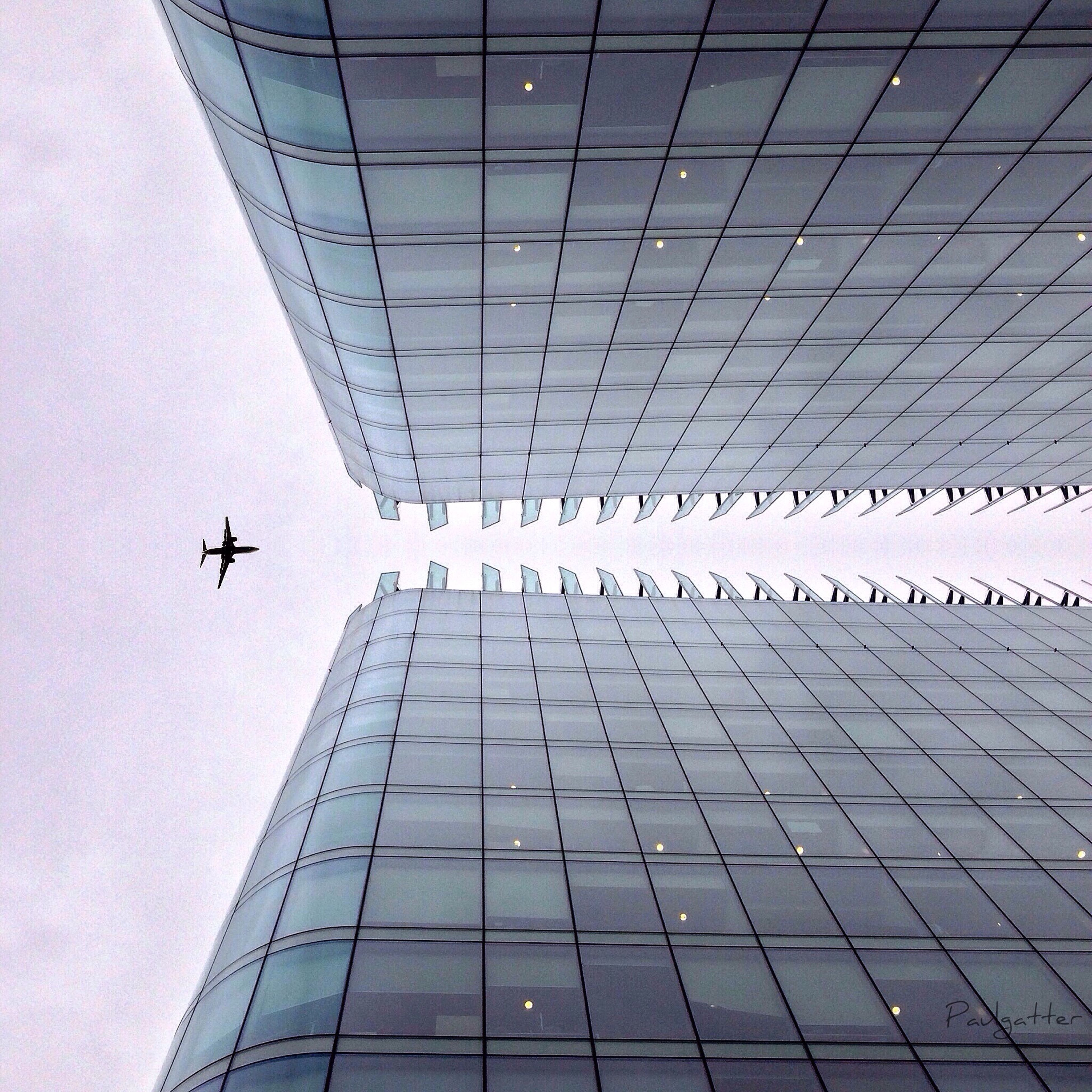 architecture, transportation, built structure, low angle view, modern, airplane, flying, mode of transport, travel, air vehicle, building exterior, airport, city, sky, day, on the move, public transportation, office building, tall - high, outdoors