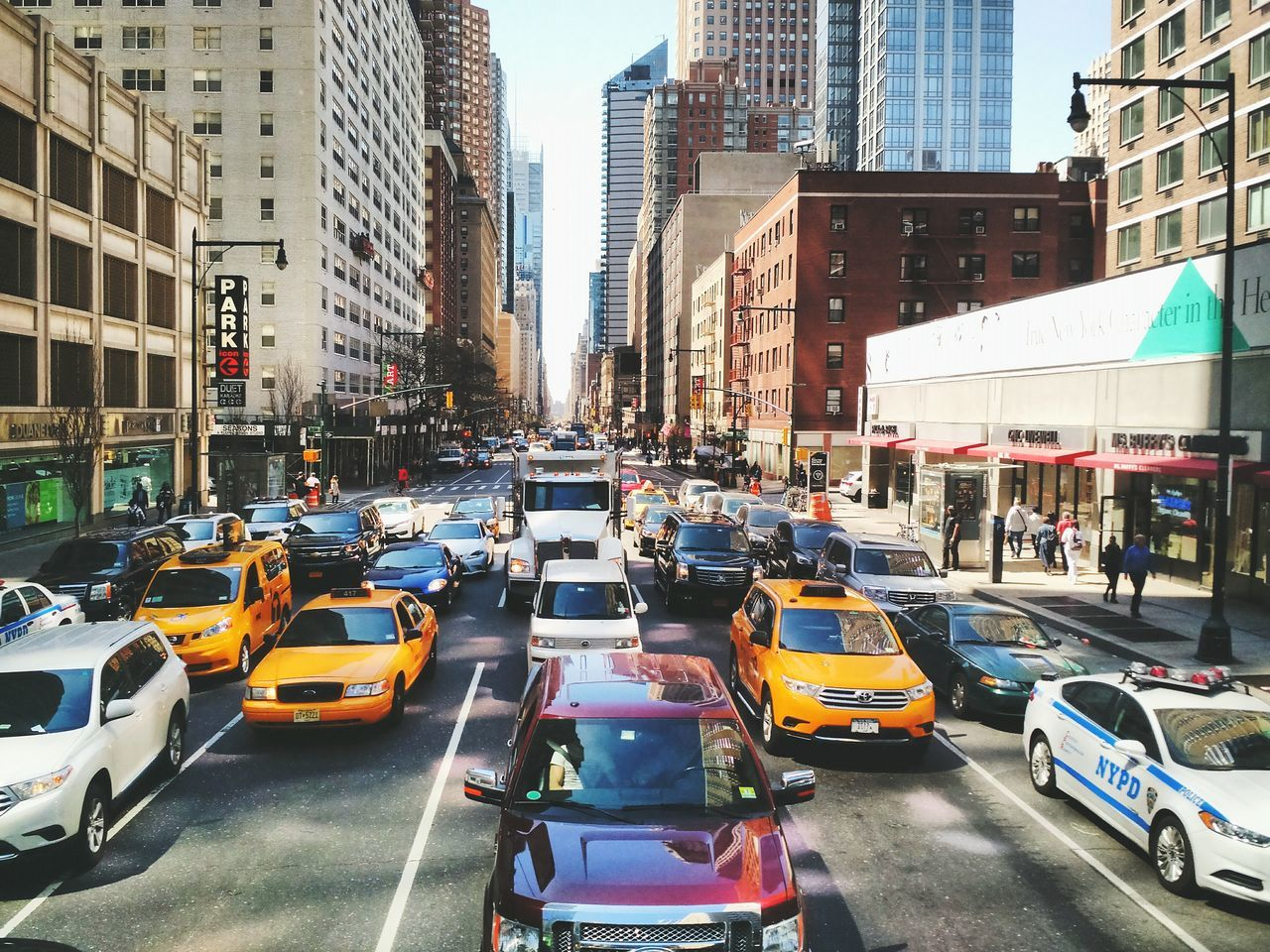 architecture, car, city, transportation, building exterior, city life, land vehicle, built structure, road, street, traffic, skyscraper, yellow taxi, large group of people, city street, mode of transport, taxi, outdoors, day, travel destinations, modern, cityscape, people