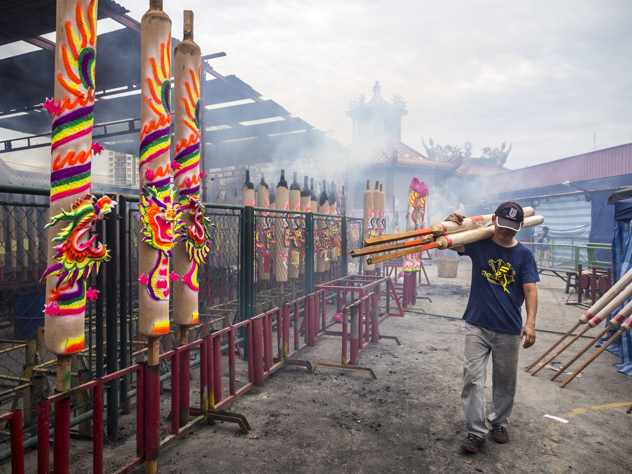 A man carrying large joss sticks on his shoulder at a Chinese temple Adult Burning Chinese Chinese Temple Full Length Joss Sticks Man Nine Emperor Festival Nine Emperor Gods Festival One Person Outdoors Smoke Smoke - Physical Structure Smoky The Photojournalist - 2017 EyeEm Awards