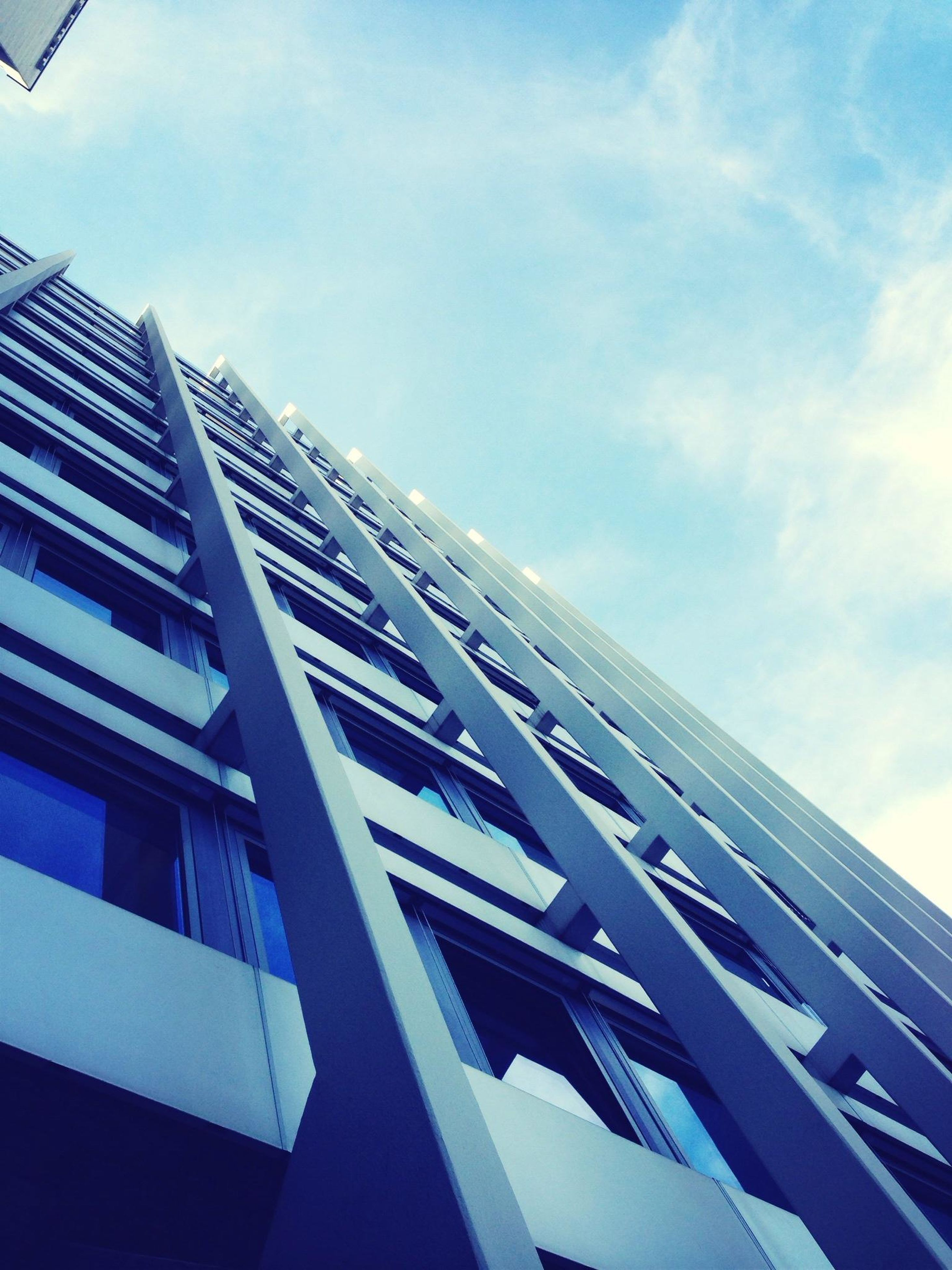 architecture, building exterior, low angle view, built structure, modern, office building, city, building, sky, skyscraper, tall - high, glass - material, window, tower, day, reflection, outdoors, no people, blue, residential building