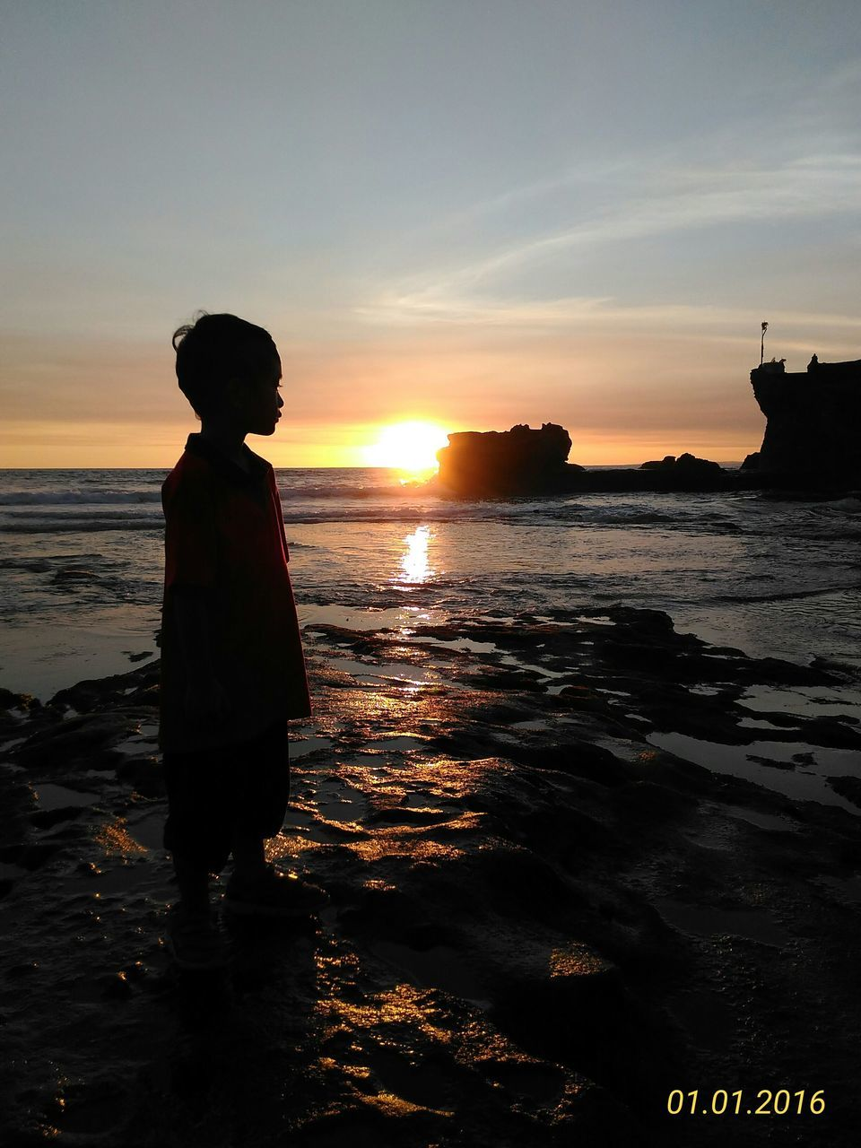 sunset, sea, silhouette, beach, real people, childhood, one person, standing, water, boys, full length, sun, sky, nature, beauty in nature, outdoors, scenics, horizon over water