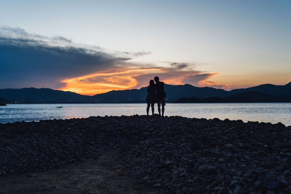 Beach Beauty In Nature Bonding Day Friendship Full Length Leisure Activity Lifestyles Love Men Mountain Nature Outdoors Real People Scenics Sea Silhouette Sky Standing Sunset Togetherness Tranquil Scene Tranquility Two People Water