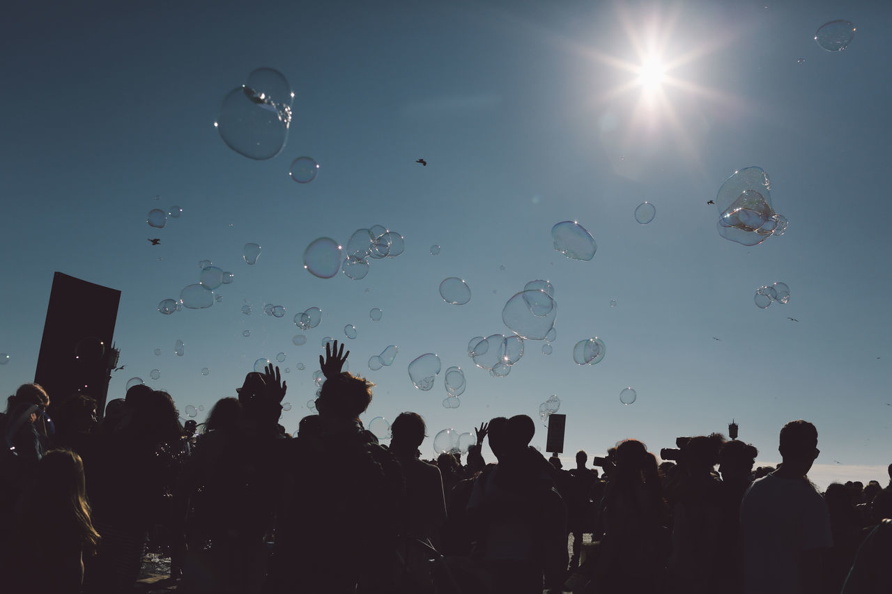 Low Angle View Of People And Bubbles Against Sky On Sunny Day