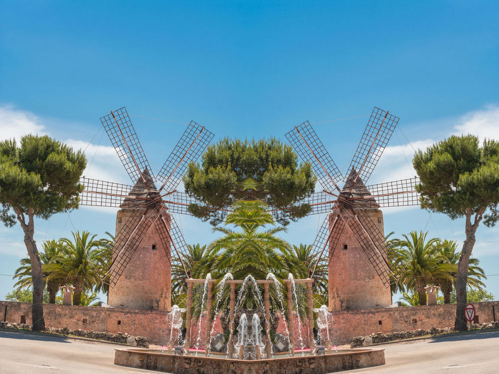 Photomontage, two old historic windmill at a country estate in Mallorca (Spain) Architecture Building Exterior Built Structure City Day Floriculture Fountains Low Angle View No People Outdoors Sky Spain Windmills Tree Two Water Promotion Wind Turbine Windmill