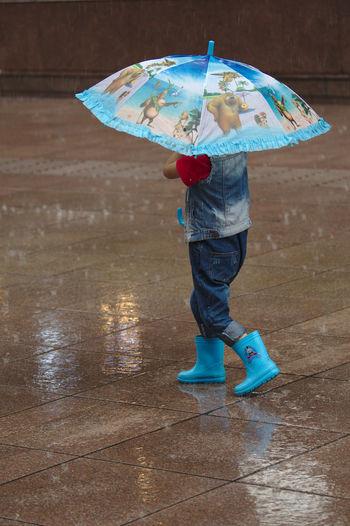 Blue Boots Boys Casual Clothing Childhood Enjoyment Full Length Holding Leisure Activity Lifestyles One Person Protection Rain Umbrella Umbrella Revolution Umbrellas Weather Wet