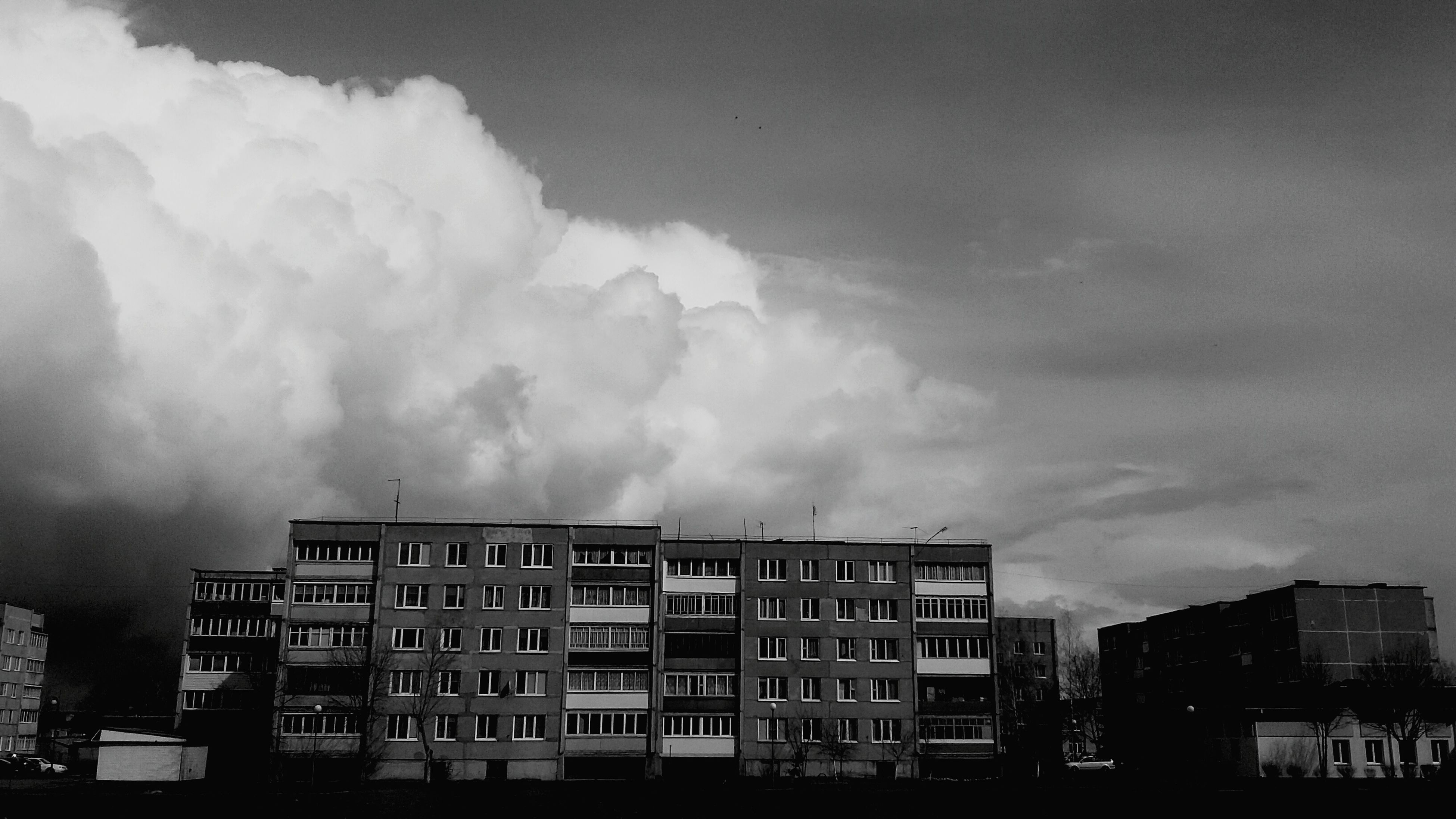 building exterior, architecture, built structure, sky, cloud - sky, cloudy, city, overcast, weather, residential building, low angle view, building, storm cloud, residential structure, cloud, outdoors, no people, apartment, dusk, residential district