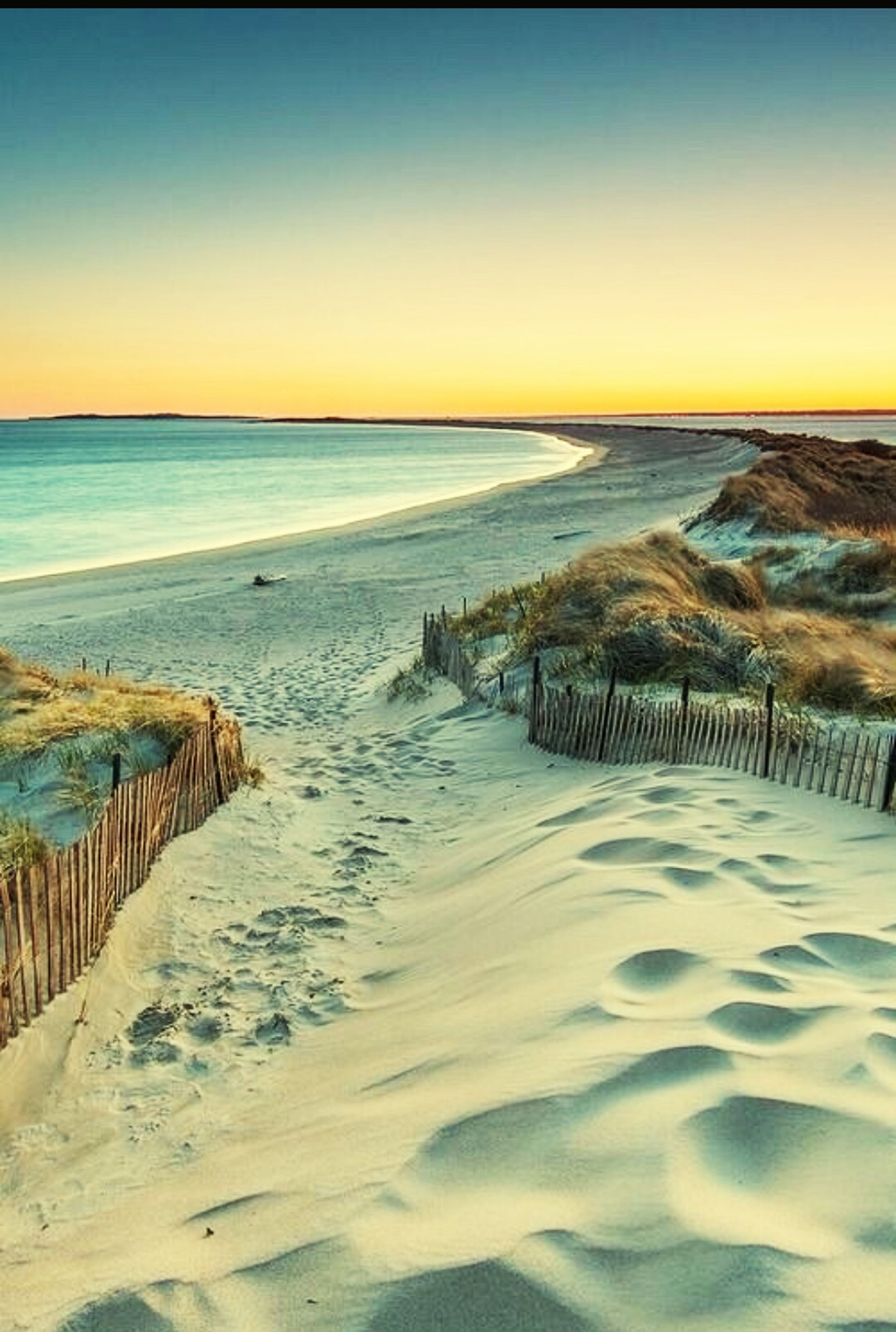 sea, beach, horizon over water, water, scenics, sand, sunset, tranquil scene, tranquility, beauty in nature, shore, idyllic, clear sky, non-urban scene, nature, tourism, vacations, travel destinations, calm, outdoors, coastline, sky, summer, wave, majestic, blue, boardwalk, remote, no people, seascape, coastal feature
