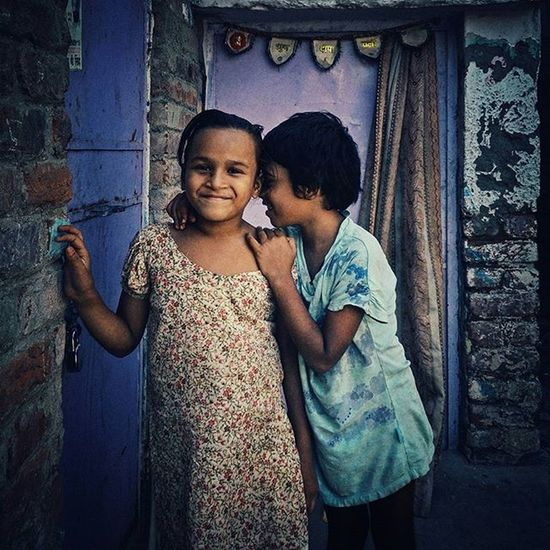 """Two Indian girls pose for a photo at Katputli Nagar in Delhi, India. The one on the right was too shy to look into the camera but wanted to be in the picture nonetheless.(5/5) Many a times, I have been approached by kids urging me to take pictures of them. They shout, """"Ek photo! Ek photo!"""" (One photo, one photo). The glee on their faces at the prospect of getting photographed makes me more than happy to oblige. After photographing the children, I realised that their expressions and their poses make the pictures special to me. Everydayeverywhere Everydayindia Dailylife Photojournalism Journalism Reportage Reportagespotlight Cityofcities Huffpostgram Indiaphotoproject Dfordelhi Sodelhi DelhiGram Onepluslife Oneplus2 Myfeatureshoot Delhi Newdelhi ASIA India"""