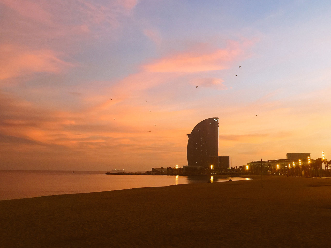sunset, architecture, built structure, sea, sky, building exterior, travel destinations, silhouette, cloud - sky, water, no people, skyscraper, nature, outdoors, city, beach, modern, scenics, horizon over water, beauty in nature, cityscape, day
