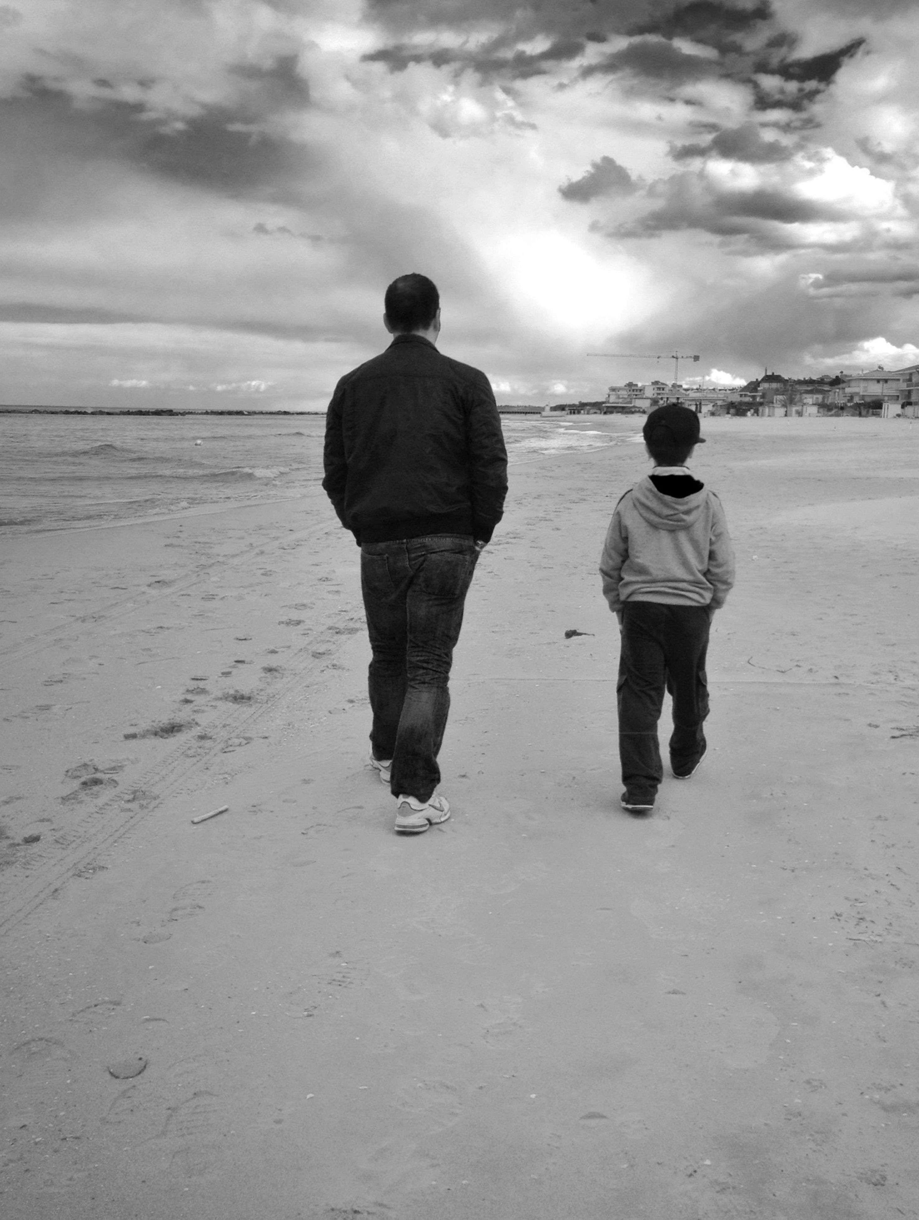 sky, rear view, beach, full length, lifestyles, cloud - sky, sand, leisure activity, sea, casual clothing, shore, standing, men, walking, childhood, cloudy, cloud